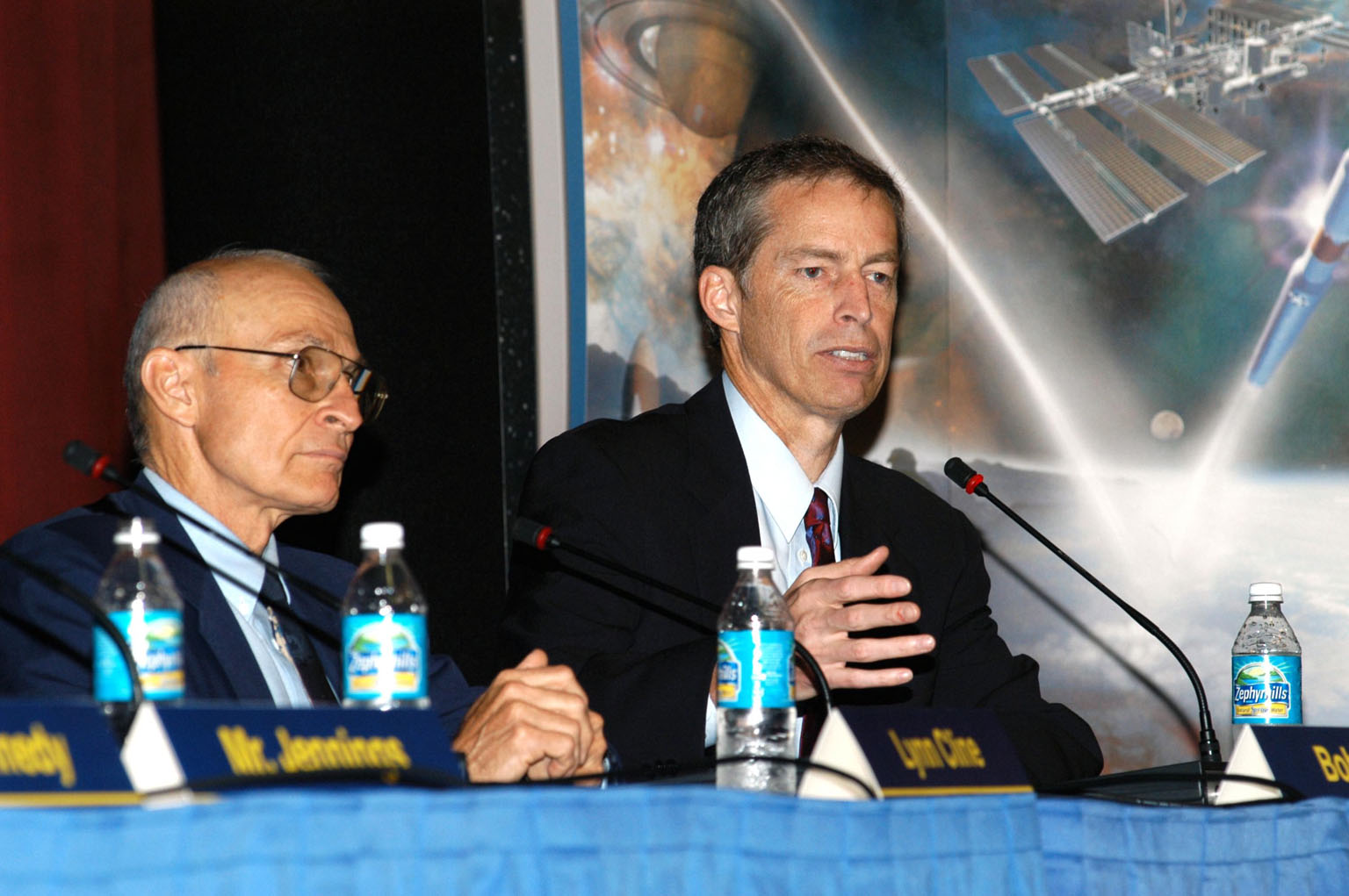 KENNEDY SPACE CENTER, FLA. -- Bob Sieck (left), former Director of Space Shuttle Processing at KSC, looks on as Jim Wetherbee, astronaut and Technical Assistant to the Director of Safety and Mission Assurance at Johnson Space Center, responds to a question asked by a member of the audience attending the Culture Change Process All Hands Meeting in the Training Auditorium. The purpose of the meeting was for employees to gain further insight into the Agency?s Vision for Space Exploration and the direction cultural change will take at KSC in order to assume its role within this vision. Other panel members were James W. Kennedy, KSC director; Jim Jennings, Deputy Associate Administrator for Institutions and Asset Management; and Lynn Cline, Deputy Associate Administrator for Space Flight.