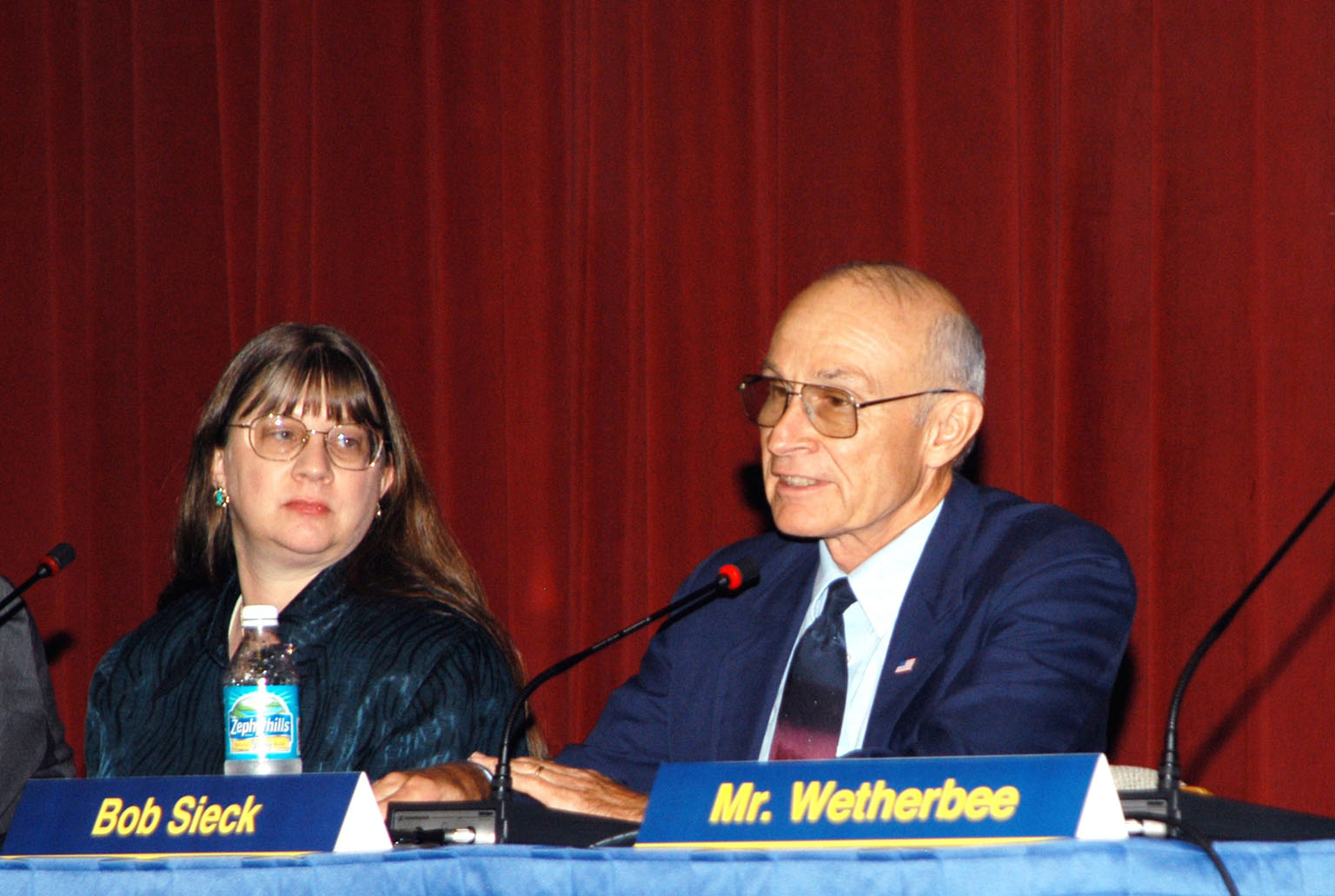 KENNEDY SPACE CENTER, FLA. -- Lynn Cline (left), Deputy Associate Administrator for Space Flight, looks on as Bob Sieck, former Director of Space Shuttle Processing at KSC, answers a question posed by a member of the audience attending the Culture Change Process All Hands Meeting in the Training Auditorium. The purpose of the meeting was for employees to gain further insight into the Agency?s Vision for Space Exploration and the direction cultural change will take at KSC in order to assume its role within this vision. Other panel members were James W. Kennedy, KSC director; Jim Jennings, Deputy Associate Administrator for Institutions and Asset Management; and Jim Wetherbee, astronaut and Technical Assistant to the Director of Safety and Mission Assurance at Johnson Space Center.