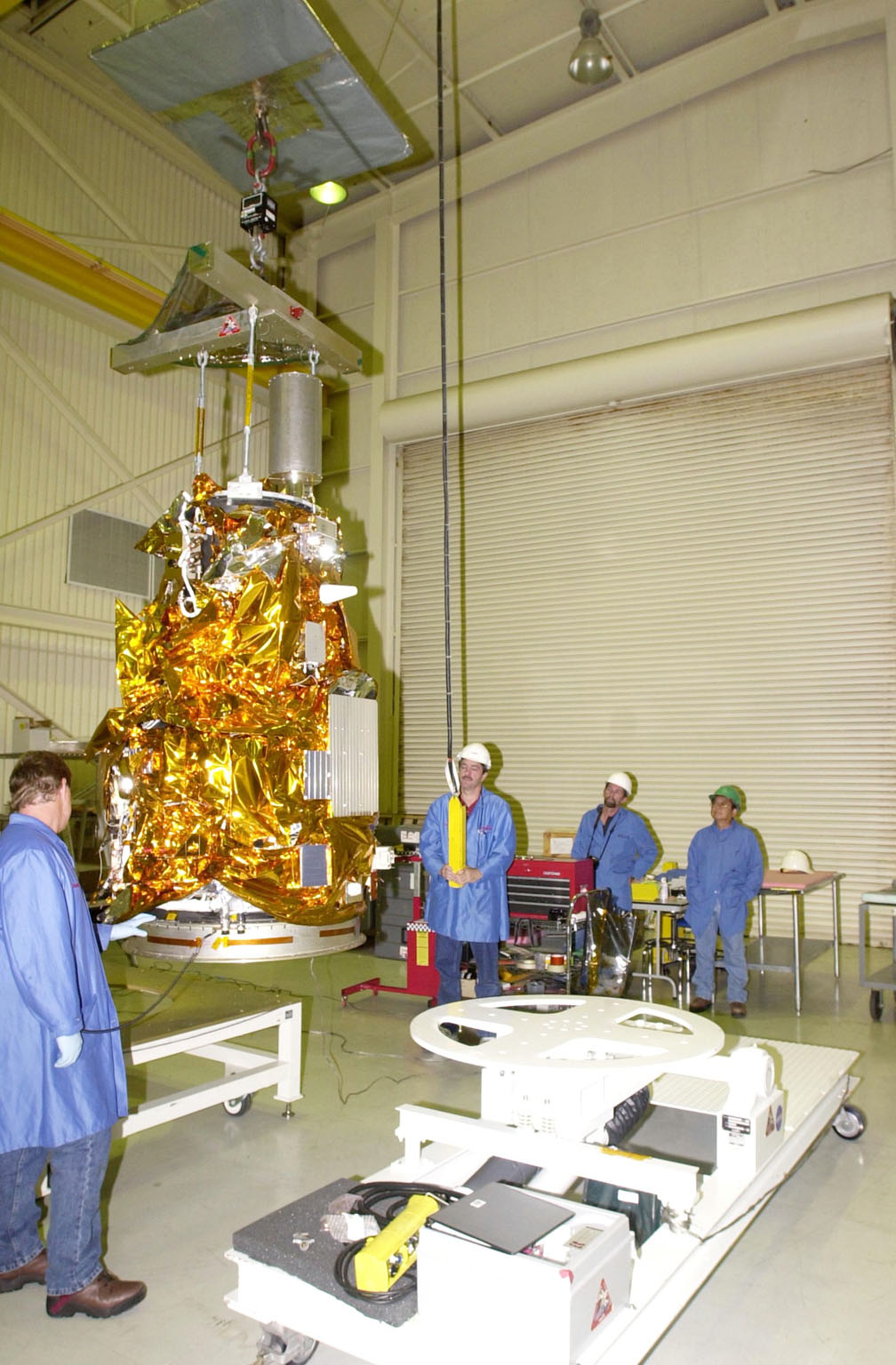 KENNEDY SPACE CENTER, FLA. - At Vandenberg Air Force Base in California, workers stand by while an overhead crane moves the Demonstration of Autonomous Rendezvous Technology (DART) spacecraft onto the mobile stand at right. DART was designed and built for NASA by Orbital Sciences Corporation as an advanced flight demonstrator to locate and maneuver near an orbiting satellite. DART weighs about 800 pounds and is nearly 6 feet long and 3 feet in diameter. The Orbital Sciences Pegasus XL will launch DART into a circular polar orbit of approximately 475 miles. DART is designed to demonstrate technologies required for a spacecraft to locate and rendezvous, or maneuver close to, other craft in space. Results from the DART mission will aid in the development of NASA?s Crew Exploration Vehicle and will also assist in vehicle development for crew transfer and crew rescue capability to and from the International Space Station.