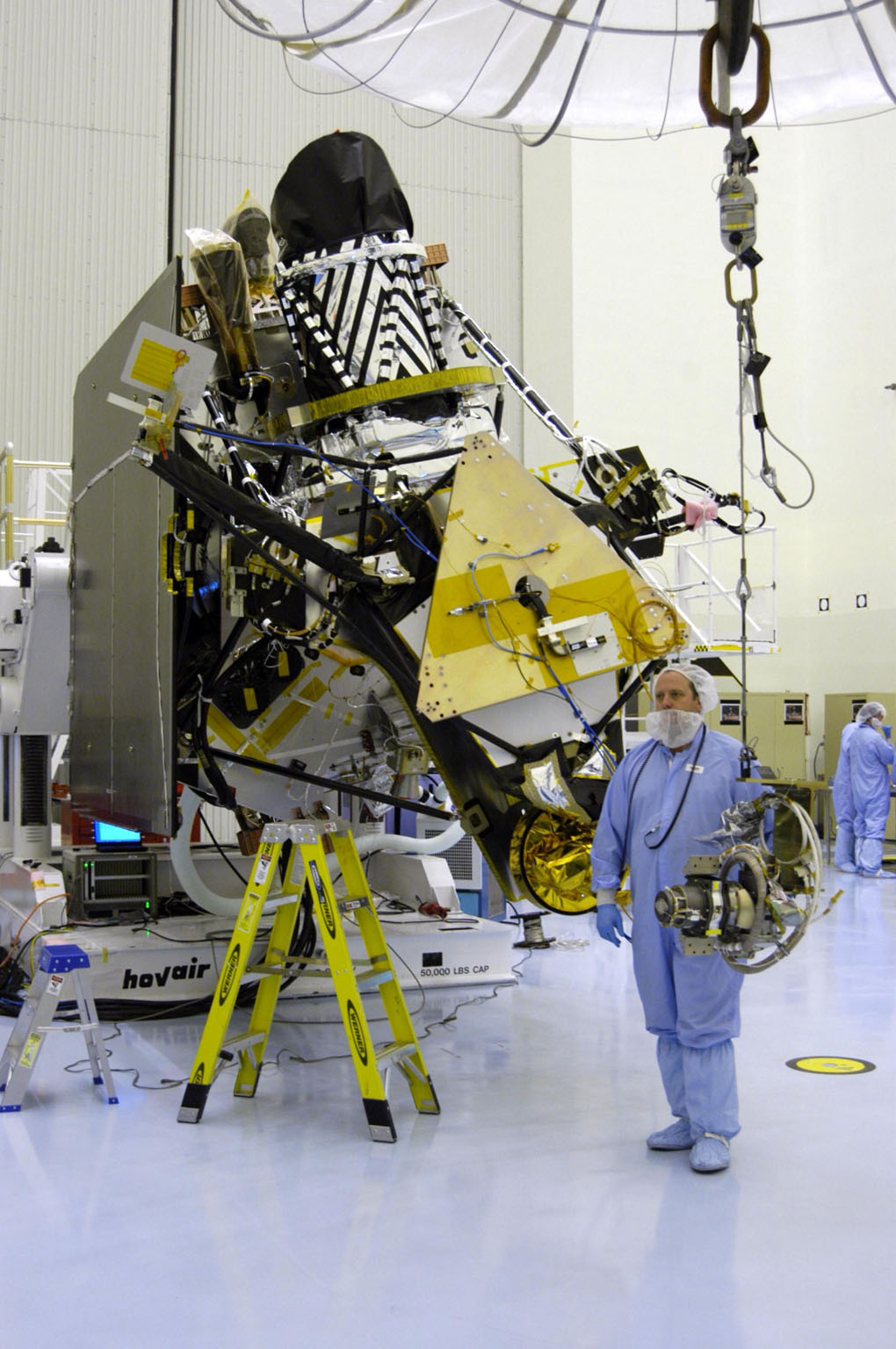 KENNEDY SPACE CENTER, FLA. - In the Payload Hazardous Servicing Facility at NASA?s Kennedy Space Center, a worker guides the gimbal across the floor to the Mars Reconnaissance Orbiter (MRO) in the background. The gimbal will be installed on the MRO solar panel. A gimbal is an appliance that allows an object to remain horizontal even as its support tips. In the PHSF, the spacecraft will undergo multiple mechanical assembly operations and electrical tests to verify its readiness for launch. A major deployment test will check out the spacecraft?s large solar arrays. The MRO was built by Lockheed Martin for NASA?s Jet Propulsion Laboratory in California. It is the next major step in Mars exploration and scheduled for launch from Cape Canaveral Air Force Station in a window opening Aug. 10. The MRO is an important next step in fulfilling NASA?s vision of space exploration and ultimately sending human explorers to Mars and beyond.