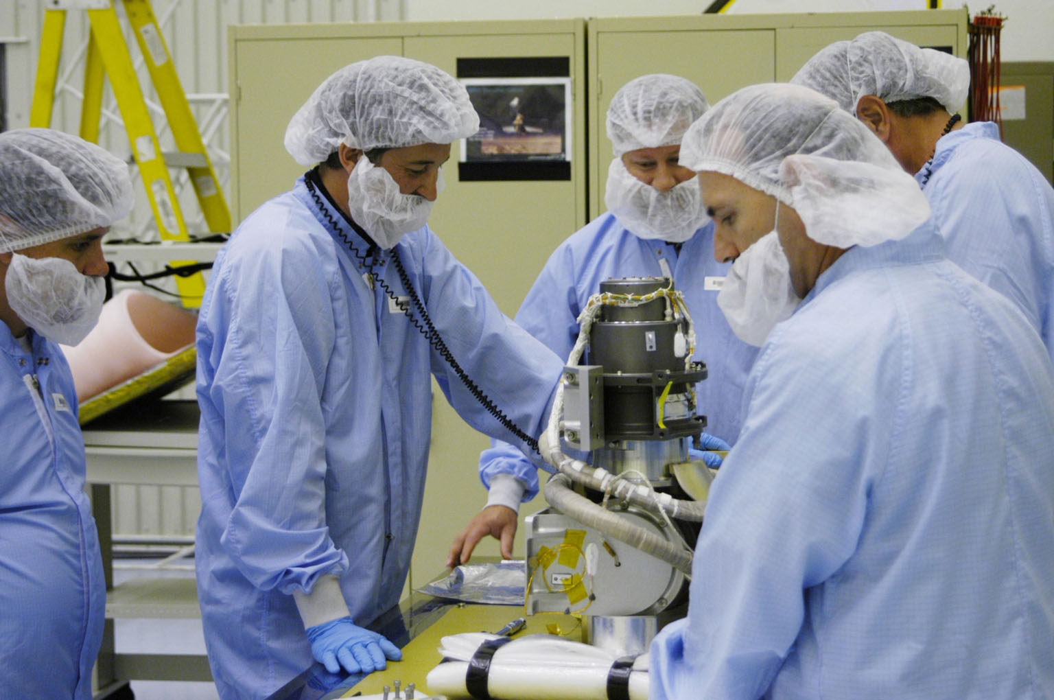 KENNEDY SPACE CENTER, FLA. - In the Payload Hazardous Servicing Facility at NASA?s Kennedy Space Center, engineers prepare to install the gimbal on the Mars Reconnaissance Orbiter (MRO) solar panel. A gimbal is an appliance that allows an object to remain horizontal even as its support tips. In the PHSF, the spacecraft will undergo multiple mechanical assembly operations and electrical tests to verify its readiness for launch. A major deployment test will check out the spacecraft?s large solar arrays. The MRO was built by Lockheed Martin for NASA?s Jet Propulsion Laboratory in California. It is the next major step in Mars exploration and scheduled for launch from Cape Canaveral Air Force Station in a window opening Aug. 10. The MRO is an important next step in fulfilling NASA?s vision of space exploration and ultimately sending human explorers to Mars and beyond.