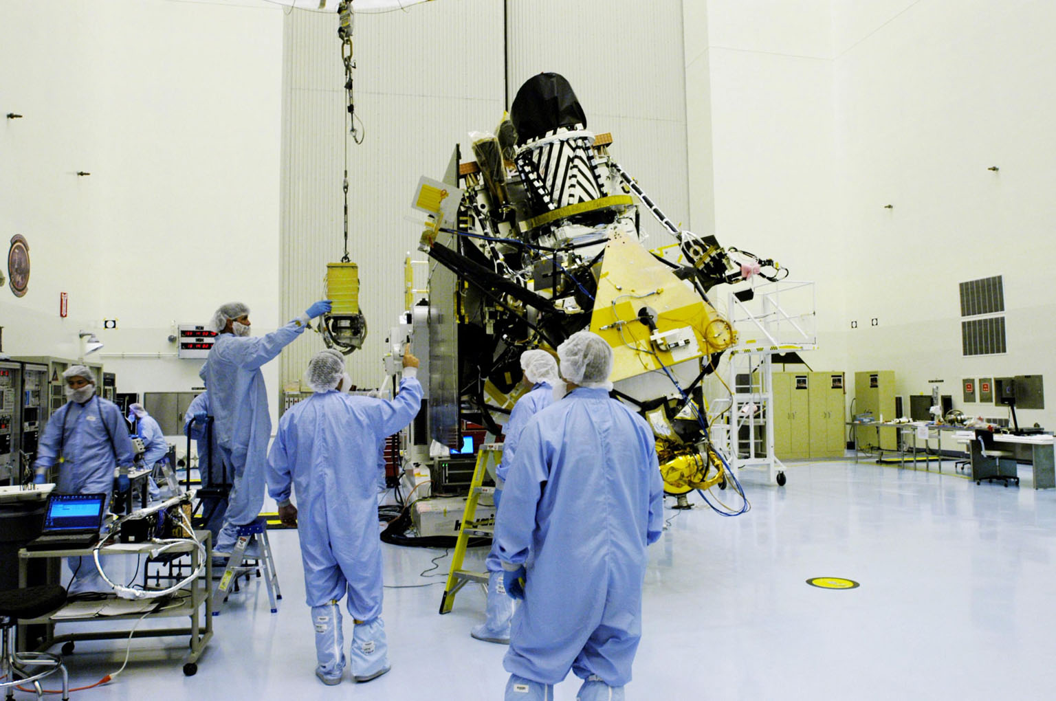 KENNEDY SPACE CENTER, FLA. - In the Payload Hazardous Servicing Facility at NASA?s Kennedy Space Center, engineers move the gimbal closer to the Mars Reconnaissance Orbiter (MRO) in the background. The gimbal will be installed on the MRO solar panel. A gimbal is an appliance that allows an object to remain horizontal even as its support tips. In the PHSF, the spacecraft will undergo multiple mechanical assembly operations and electrical tests to verify its readiness for launch. A major deployment test will check out the spacecraft?s large solar arrays. The MRO was built by Lockheed Martin for NASA?s Jet Propulsion Laboratory in California. It is the next major step in Mars exploration and scheduled for launch from Cape Canaveral Air Force Station in a window opening Aug. 10. The MRO is an important next step in fulfilling NASA?s vision of space exploration and ultimately sending human explorers to Mars and beyond.