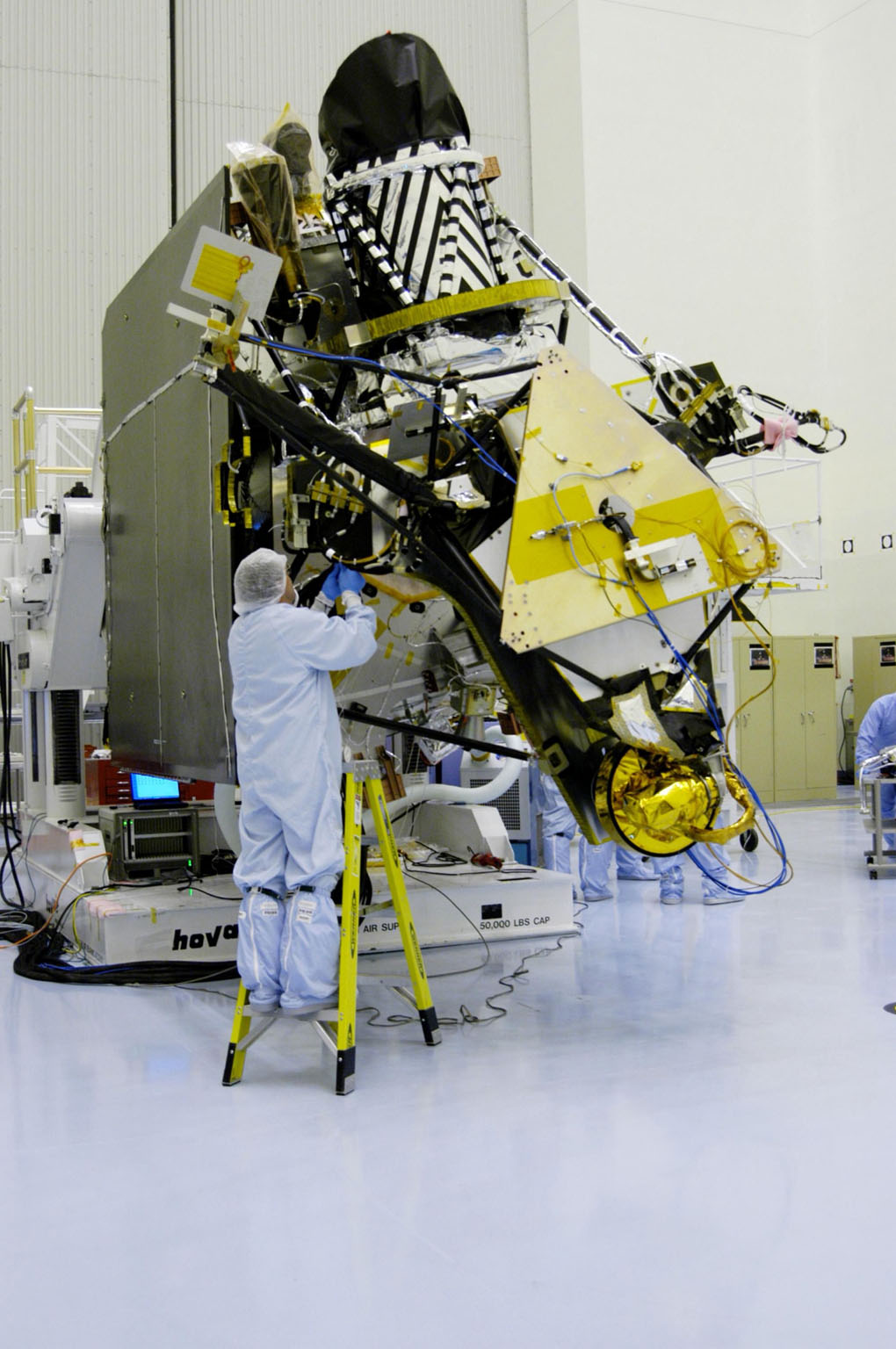 KENNEDY SPACE CENTER, FLA. - In the Payload Hazardous Servicing Facility at NASA?s Kennedy Space Center, an engineer installs a second gimbal on a Mars Reconnaissance Orbiter (MRO) solar panel. A gimbal is an appliance that allows an object to remain horizontal even as its support tips. In the PHSF, the spacecraft will undergo multiple mechanical assembly operations and electrical tests to verify its readiness for launch. A major deployment test will check out the spacecraft?s large solar arrays. The MRO was built by Lockheed Martin for NASA?s Jet Propulsion Laboratory in California. It is the next major step in Mars exploration and scheduled for launch from Cape Canaveral Air Force Station in a window opening Aug. 10. The MRO is an important next step in fulfilling NASA?s vision of space exploration and ultimately sending human explorers to Mars and beyond.