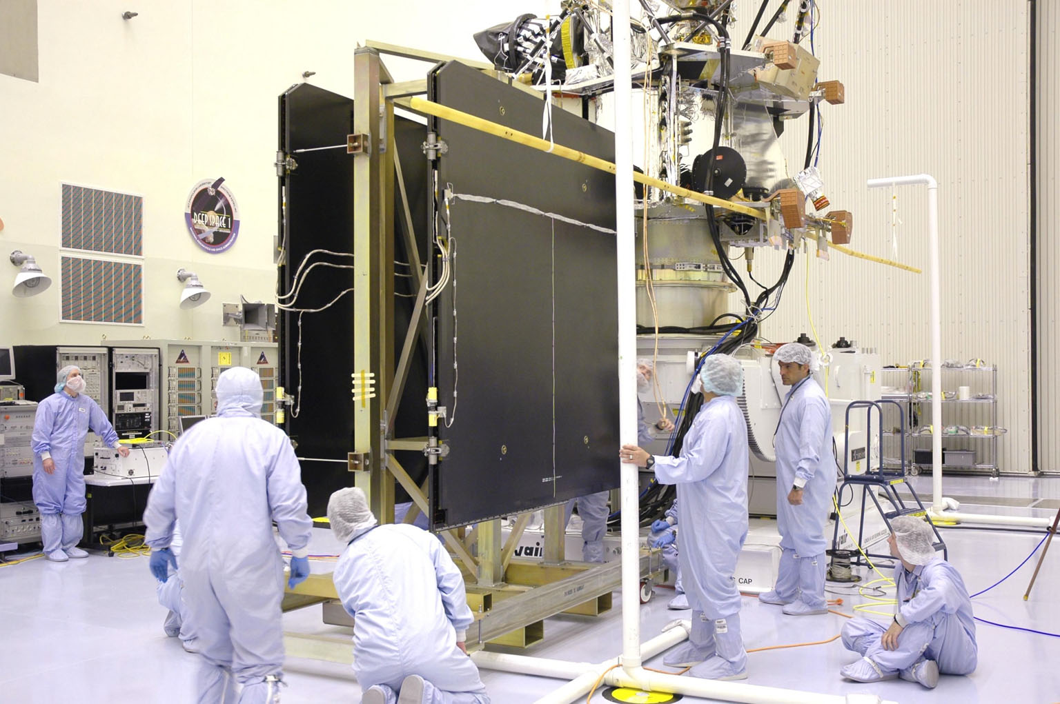 KENNEDY SPACE CENTER, FLA. - In the Payload Hazardous Servicing Facility, technicians prepare the solar arrays for the Mars Reconnaissance Orbiter (MRO) and an antenna simulator (yellow horizontal rod) for an electromagnetic interference verification test. If no interference is found during the test, the Shallow Radar Antenna (SHARAD) will be installed on the spacecraft. The spacecraft is undergoing multiple mechanical assembly operations and electrical tests to verify its readiness for launch. The MRO was built by Lockheed Martin for NASA?s Jet Propulsion Laboratory in California. It is the next major step in Mars exploration and scheduled for launch from Launch Complex 41 at Cape Canaveral Air Force Station in a window opening Aug. 10. The MRO is an important next step in fulfilling NASA?s vision of space exploration and ultimately sending human explorers to Mars and beyond.