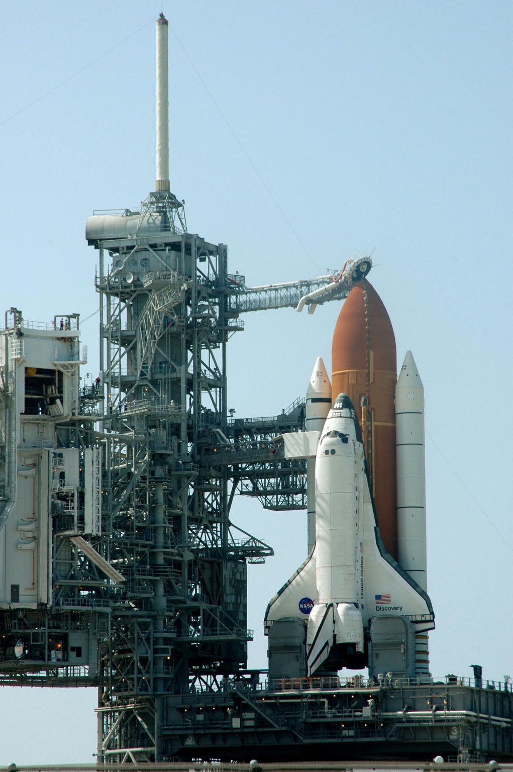 KENNEDY SPACE CENTER, FLA. - Space Shuttle Discovery in full launch configuration is revealed after the Rotating Service Structure (RSS) is rotated back at Launch Pad 39B at NASA Kennedy Space Center. The gaseous oxygen vent arm (beanie cap) has been extended to the top of the External Tank. Rollback of the RSS is a major preflight milestone, typically occurring during the T-11-hour hold on L-1 (the day before launch). Discovery is scheduled to lift off on the historic Return to Flight mission STS-114 at 10:39 a.m. EDT July 26 with a crew of seven. On the mission to the International Space Station the crew will perform inspections on orbit for the first time of all of the Reinforced Carbon-Carbon (RCC) panels on the leading edge of the wings and the Thermal Protection System tiles using the new Canadian-built Orbiter Boom Sensor System and the data from 176 impact and temperature sensors. Mission Specialists will also practice repair techniques on RCC and tile samples during a spacewalk in the payload bay. During two additional spacewalks, the crew will install the External Stowage Platform-2, equipped with spare part assemblies, and a replacement Control Moment Gyroscope contained in the Lightweight Multi-Purpose Experiment Support Structure.