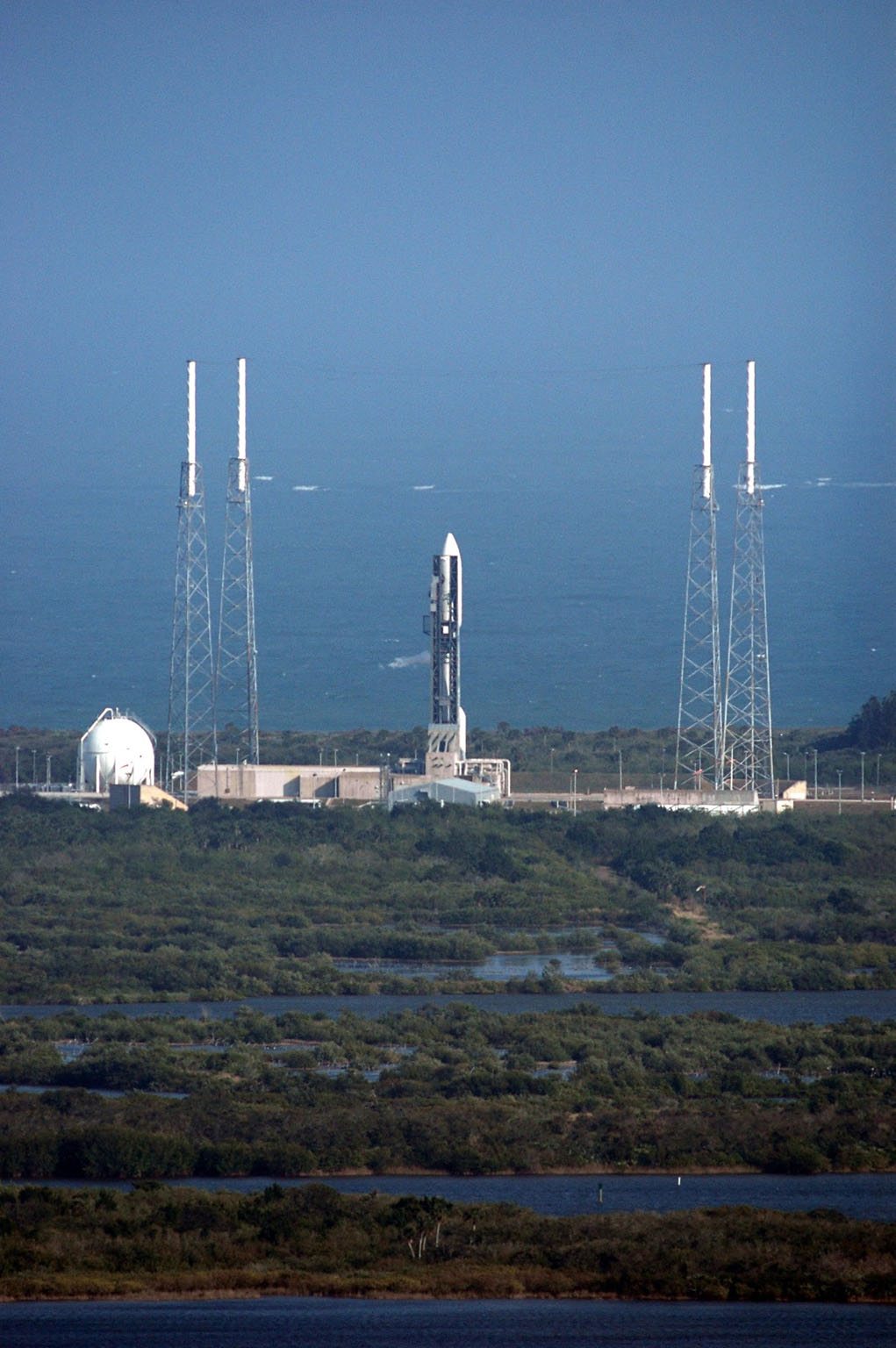 KENNEDY SPACE CENTER, FLA. - The Atlas V rocket with the New Horizons spacecraft on top sits waiting on the launch pad at Complex 41 at Cape Canaveral Air Force Station in Florida. The view is from the top of the Vehicle Assembly Building at NASA Kennedy Space Center. Surrounding the launch vehicle are four lightning masts. The launch on this date was scrubbed due to high surface winds in the area and has been rescheduled for 1:16 p.m. EST Jan. 18. The compact, 1,050-pound piano-sized probe will get a boost from a kick-stage solid propellant motor for its journey to Pluto. New Horizons will be the fastest spacecraft ever launched, reaching lunar orbit distance in just nine hours and passing Jupiter 13 months later. The launch at this time allows New Horizons to fly past Jupiter in early 2007 and use the planet?s gravity as a slingshot toward Pluto. The Jupiter flyby trims the trip to Pluto by as many as five years and provides opportunities to test the spacecraft?s instruments and flyby capabilities on the Jupiter system. New Horizons could reach the Pluto system as early as mid-2015, conducting a five-month-long study possible only from the close-up vantage of a spacecraft. Photo credit: NASA/Kim Shiflett