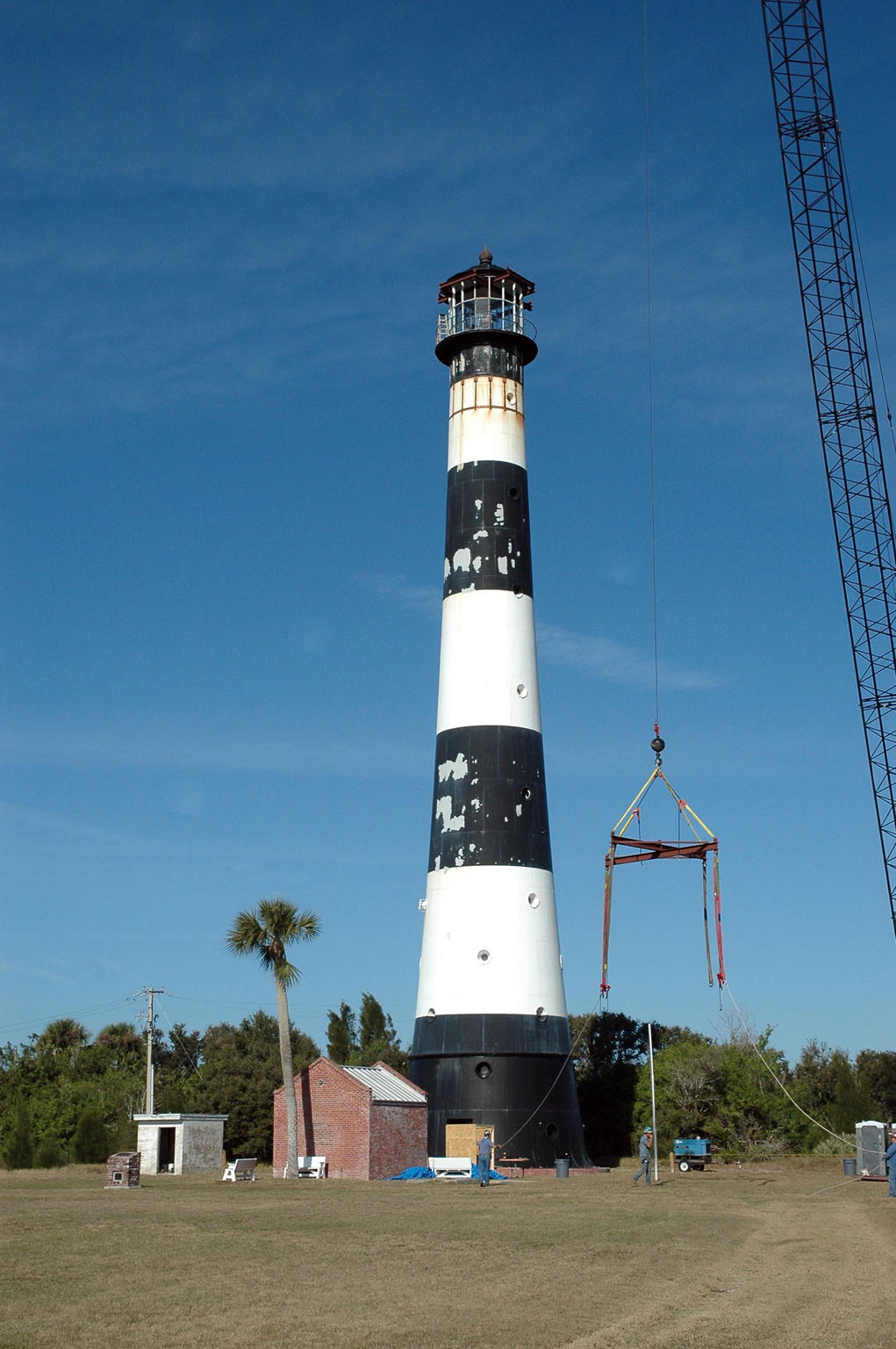 KENNEDY SPACE CENTER, FLA. - At Cape Canaveral Air Force Station, a crane is lifted near the Cape Canaveral Lighthouse for use in removing the lamp room at top. Leaks in the roof allowed moisture to seep in. The lamp room is being removed for repairs and refurbishment. In addition, the original brass roof will be restored and put back in place. The Cape Canaveral Lighthouse is the only operational lighthouse owned by the Air Force. It was first erected in 1868 near the edge of the Atlantic Ocean. Photo credit: NASA/Jack Pfaller