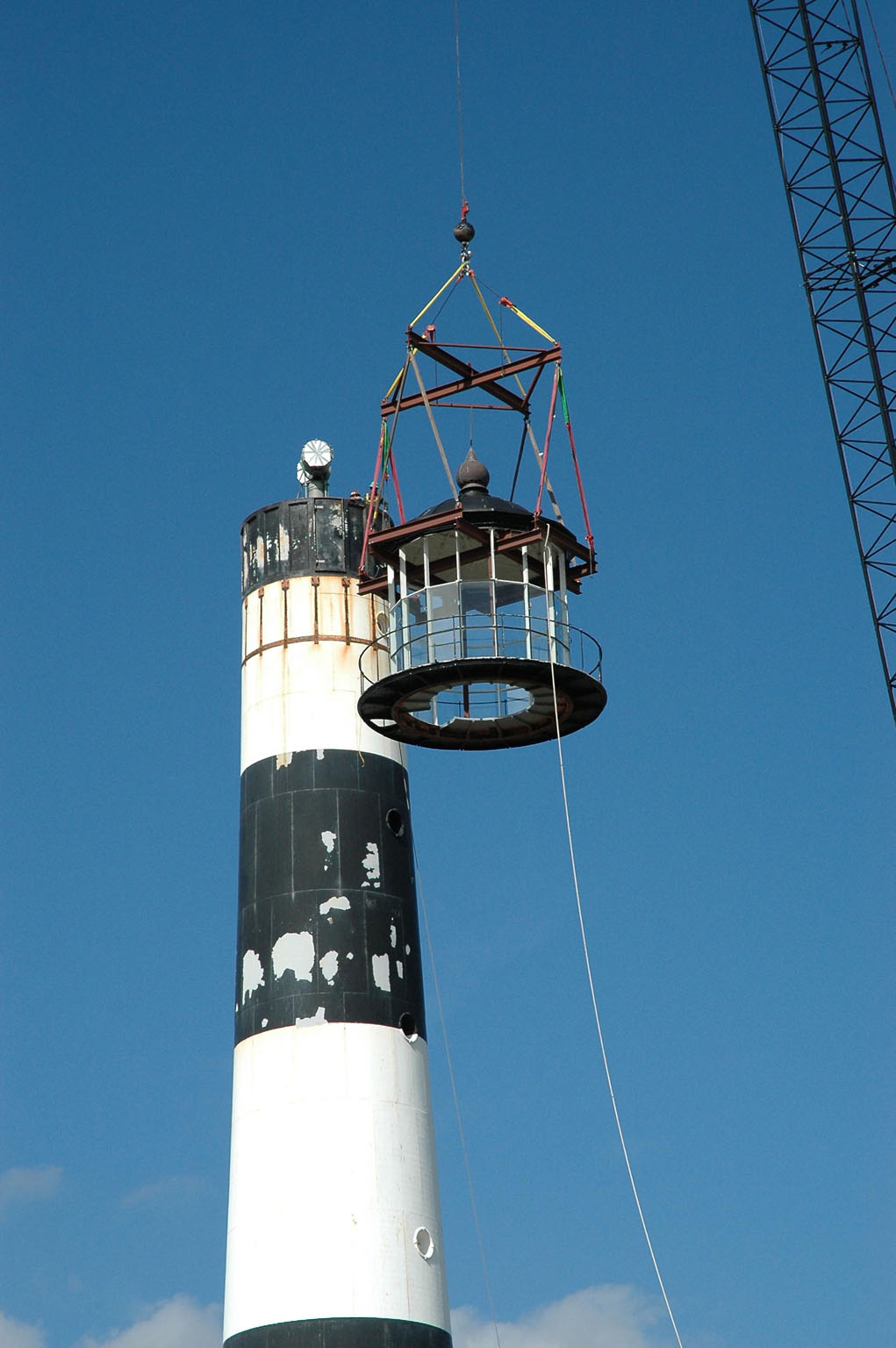 KENNEDY SPACE CENTER, FLA. - At Cape Canaveral Air Force Station, a crane lowers the detached lamp room alongside the Cape Canaveral Lighthouse. Leaks in the roof allowed moisture to seep in. The lamp room is being removed for repairs and refurbishment. In addition, the original brass roof will be restored and put back in place. The Cape Canaveral Lighthouse is the only operational lighthouse owned by the Air Force. It was first erected in 1868 near the edge of the Atlantic Ocean. Photo credit: NASA/Jack Pfaller