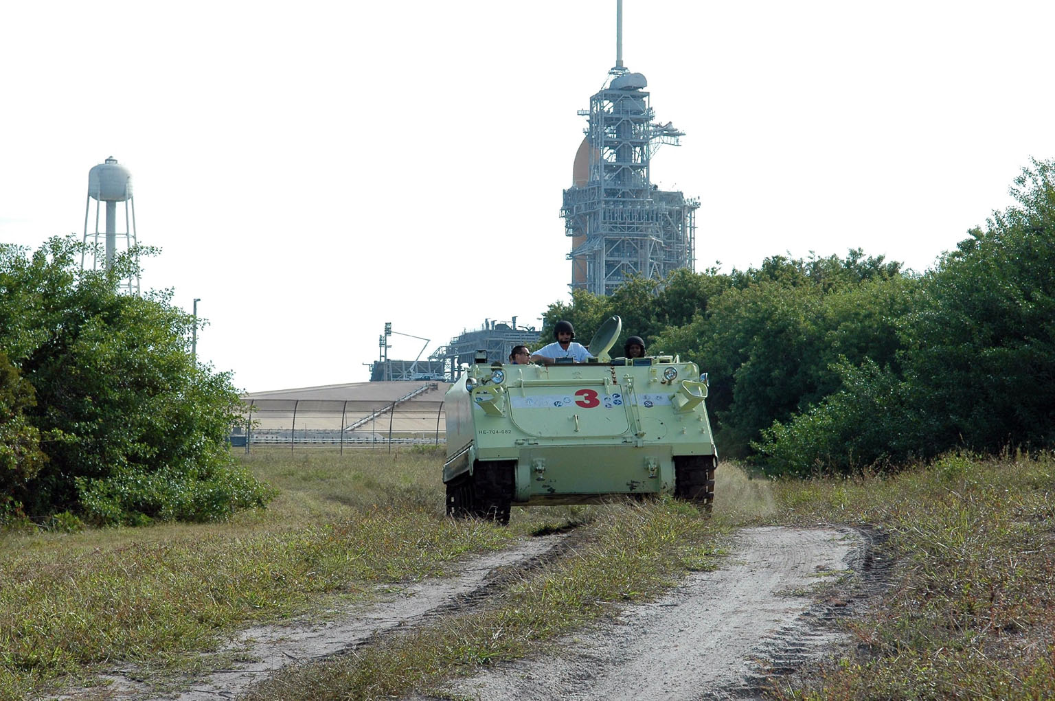 KENNEDY SPACE CENTER, FLA. -- STS-116 Mission Specialist Joan Higginbotham practices driving the M-113 armored personnel carrier away from Launch Pad 39B. On the M-113, Pilot William Oefelein is at left and Capt. George Hoggard, who is astronaut rescue team leader, in between Oefelein and Higginbotham. In the background is the fixed service structure, with the 80-foot-tall lightning mast on top, and Space Shuttle Discovery -- only the orange external tank can be seen. The mission crew is at KSC for terminal countdown demonstration test (TCDT) activities that are preparation for launch. The M-113 could be used to move the crew quickly away from the launch pad in the event of an emergency. The STS-116 mission is No. 20 to the International Space Station and construction flight 12A.1. The mission payload is the SPACEHAB module, the P5 integrated truss structure and other key components. Launch is scheduled for no earlier than Dec. 7. Photo credit: NASA/Kim Shiflett