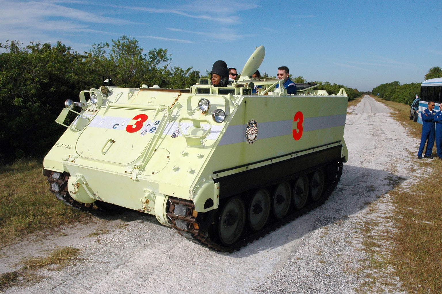 KENNEDY SPACE CENTER, FLA. -- STS-116 Mission Specialist Joan Higginbotham practices driving the M-113 armored personnel carrier. The mission crew is at KSC for terminal countdown demonstration test (TCDT) activities that are preparation for launch. The M-113 could be used to move the crew quickly away from the launch pad in the event of an emergency. In the background can be seen Pilot William Oefelein and Mission Specialist Nicholas Patrick. The STS-116 mission is No. 20 to the International Space Station and construction flight 12A.1. The mission payload is the SPACEHAB module, the P5 integrated truss structure and other key components. Launch is scheduled for no earlier than Dec. 7. Photo credit: NASA/Kim Shiflett