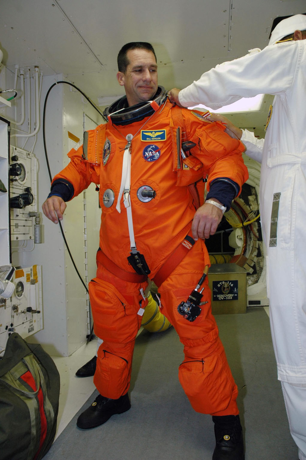 KENNEDY SPACE CENTER, FLA. -- In the white room on Launch Pad 39B, STS-116 Pilot William Oefelein is helped with his gear before entering Space Shuttle Discovery. The mission crew is taking part in a simulated launch countdown, part of the terminal countdown demonstration test that includes prelaunch preparations. The STS-116 mission is No. 20 to the International Space Station and construction flight 12A.1. The mission payload is the SPACEHAB module, the P5 integrated truss structure and other key components. Launch is scheduled for no earlier than Dec. 7. Photo credit: NASA/Amanda Diller
