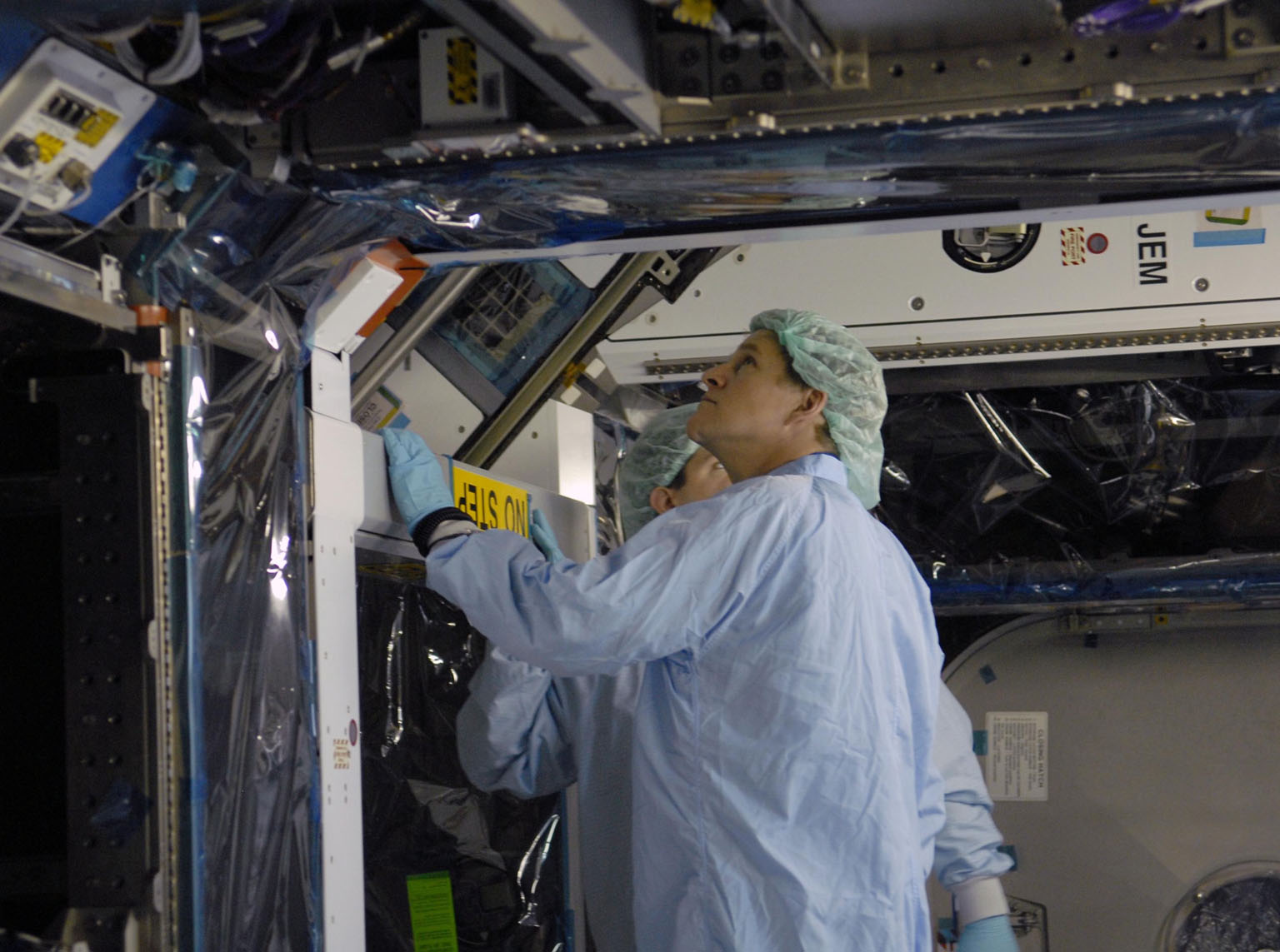 KENNEDY SPACE CENTER, FLA. -- STS-120 Mission Specialist Scott Parazynski takes a look underneath the primary payload for the mission: the U.S. Node 2, another element to be added to the International Space Station. Node 2 will provide a passageway between three station science experiment facilities: the U.S. Destiny Laboratory, the Kibo Japanese Experiment Module, and the European Columbus Laboratory. STS-120 is targeted for launch on Sept. 7 with a crew of six, including Commander Pam Melroy, Pilot George Zamka, and Mission Specialist Mike Foreman. Photo credit: NASA/Kim Shiflett