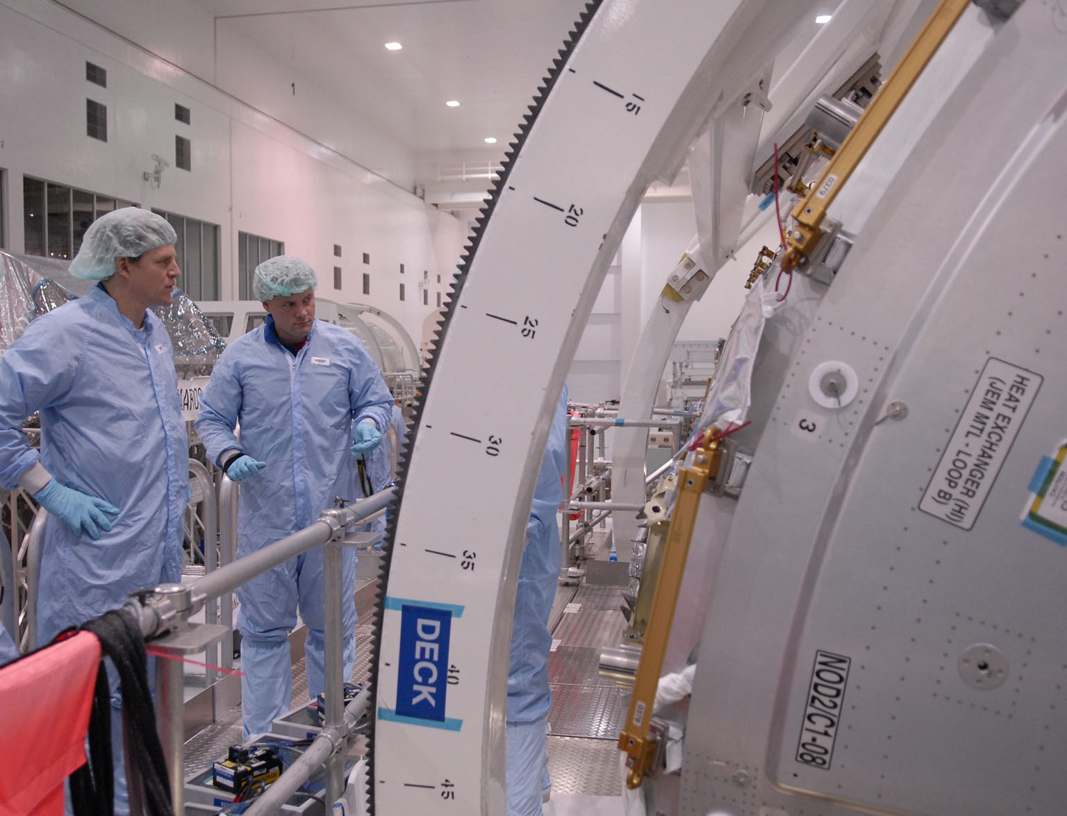 KENNEDY SPACE CENTER, FLA. -- STS-120 Mission Specialists Scott Parazynski (left) and Doug Wheelock check out the primary payload for the mission: the U.S. Node 2, another element to be added to the International Space Station. They are familiarizing themselves with the payload. Node 2 will provide a passageway between three station science experiment facilities: the U.S. Destiny Laboratory, the Kibo Japanese Experiment Module, and the European Columbus Laboratory. STS-120 is targeted for launch on Sept. 7 with a crew of six, including Commander Pam Melroy, Pilot George Zamka, and Mission Specialist Mike Foreman. Photo credit: NASA/Kim Shiflett