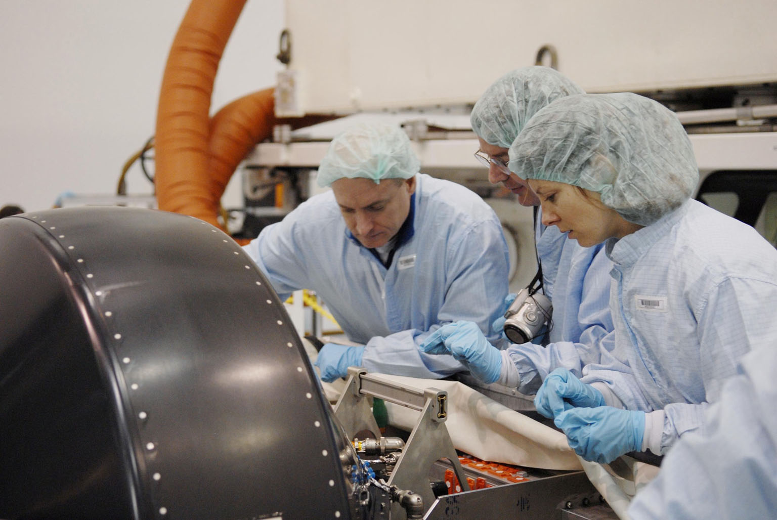 KENNEDY SPACE CENTER, FLA. -- In the Space Station Processing Facility, members of the STS-118 crew learn important information from technicians about the control moment gyro (CMG) in front of them that is part of the payload on their mission. At left is Commander Scott Kelly; at right is Mission Specialist Tracy Caldwell. The CMG will replace a faulty one on the International Space Station. The payload also includes the SPACEHAB single cargo module, the third starboard truss segment (ITS S5) and the external stowage platform 3 (ESP3). STS-118 is targeted to launch June 28 from Launch Pad 39A. Photo credit: NASA/Kim Shiflett