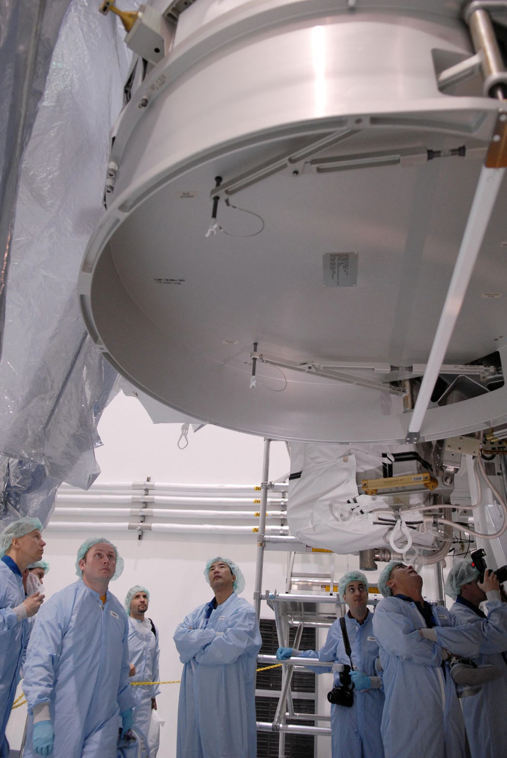 KENNEDY SPACE CENTER, FLA. -- In the foreground, astronauts Tim Kopra, Michael Fincke, Soichi Noguchi, and Salizhan Sharipov (arms foldled) peer up at the Node 2 module in the Space Station Processing Facility. They and other astronauts are familiarizing themselves with the various elements to be installed on the International Space Station on future spaceflights. With construction of the Space Station the primary focus of future shuttle missions, astronaut crews will be working with one or more of the elements and hardware already being processed in the SSPF. Photo credit: NASA/Kim Shiflett