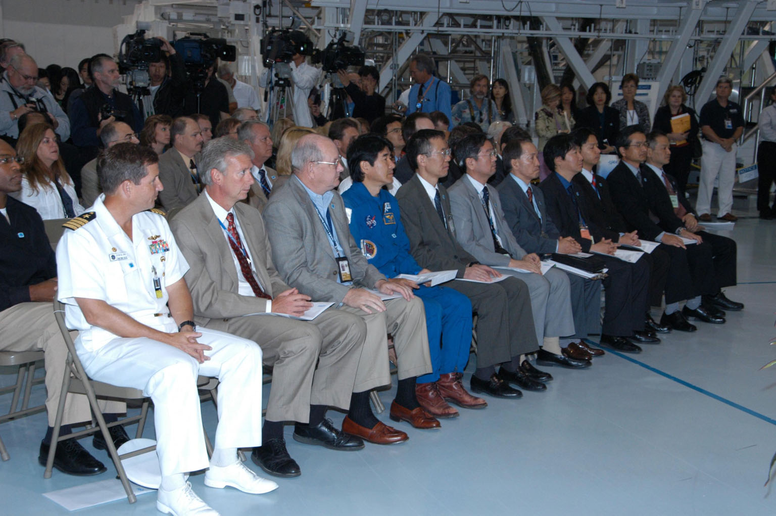 KENNEDY SPACE CENTER, FLA. -- In the Space Station Processing Facility, NASA and Japanese Aerospace and Exploration Agency (JAXA) officials welcome the arrival of the Experiment Logistics Module Pressurized Section for the Japanese Experiment Module, or JEM, to the Kennedy Space Center. Seen here at right are JAXA representatives, including Japanese astronaut Takao Doi (center of front row), who is a crew member for mission STS-123 that will deliver the module to the space station. The new International Space Station component arrived at Kennedy March 12 to begin preparations for its future launch on mission STS-123. It will serve as an on-orbit storage area for materials, tools and supplies. It can hold up to eight experiment racks and will attach to the top of another larger pressurized module. Photo credit: NASA/George Shelton