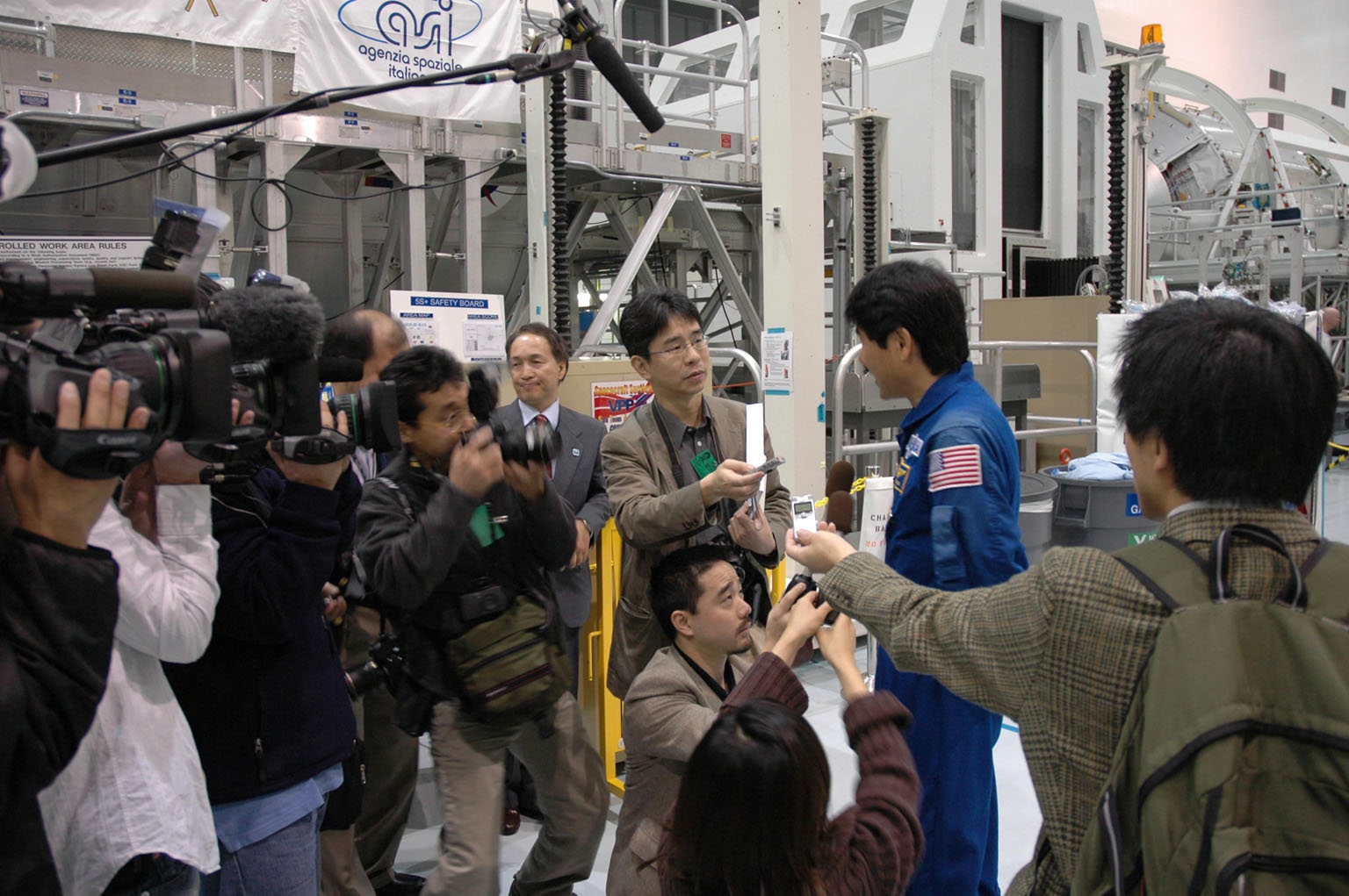 KENNEDY SPACE CENTER, FLA. -- In the Space Station Processing Facility, journalists and photographers ask Japanese astronaut Takao Doi about the Experiment Logistics Module Pressurized Section for the Japanese Experiment Module, or JEM, that he will accompany on mission STS-123 to the International Space Station. Earlier, NASA and Japanese Aerospace and Exploration Agency (JAXA) officials welcomed the arrival of the logistics module. The logistics module will serve as an on-orbit storage area for materials, tools and supplies. It can hold up to eight experiment racks and will attach to the top of another larger pressurized module. Photo credit: NASA/George Shelton