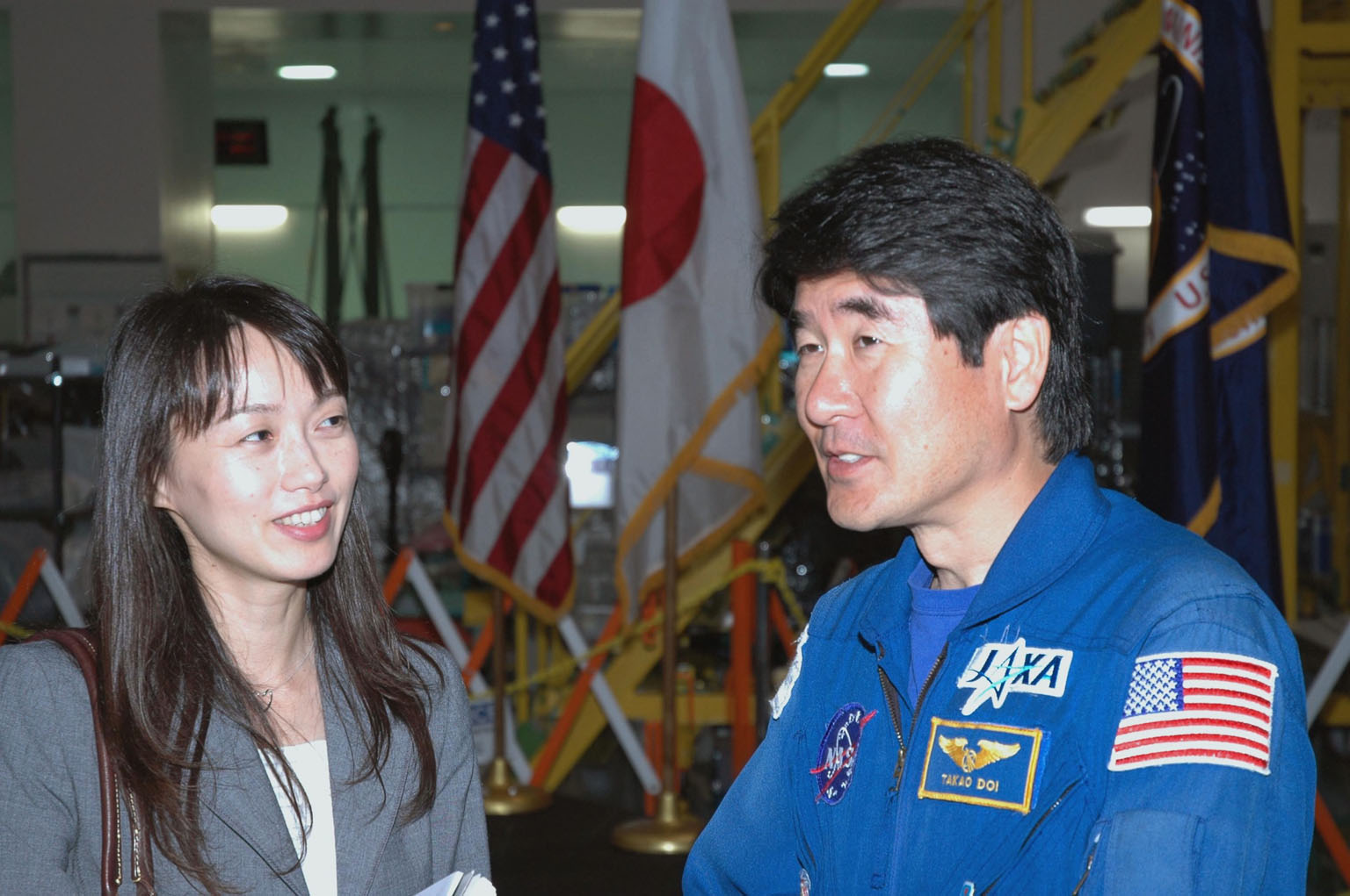 KENNEDY SPACE CENTER, FLA. -- After a welcoming ceremony for the Experiment Logistics Module Pressurized Section of the Japanese Experiment Module, astronaut Takao Doi (right) talks with Kumiko Tanabe, a public affairs representative of the Japanese Aerospace and Exploration Agency. The logistics module will be delivered to the space station on mission STS-123. Doi is a crew member on that mission.The module will serve as an on-orbit storage area for materials, tools and supplies. It can hold up to eight experiment racks and will attach to the top of another larger pressurized module. Photo credit: NASA/George Shelton