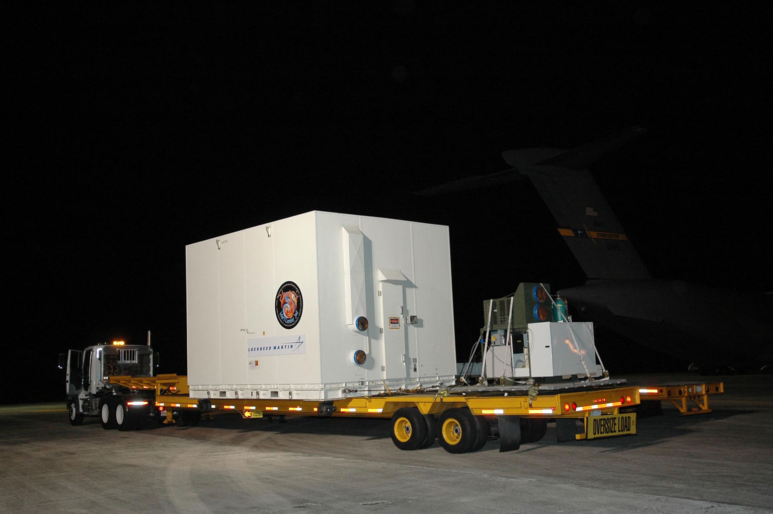 KENNEDY SPACE CENTER, FLA. -- After its arrival at Kennedy Space Center's Shuttle Landing Facility, the crated Phoenix spacecraft is secure on a flat bed truck for transportation to the Payload Hazardous Servicing Facility. The Phoenix mission is the first project in NASA's first openly competed program of Mars Scout missions. Phoenix will land in icy soils near the north polar permanent ice cap of Mars and explore the history of the water in these soils and any associated rocks, while monitoring polar climate. Landing is planned in May 2008 on arctic ground where a mission currently in orbit, Mars Odyssey, has detected high concentrations of ice just beneath the top layer of soil. It will serve as NASA's first exploration of a potential modern habitat on Mars and open the door to a renewed search for carbon-bearing compounds, last attempted with NASA?s Viking missions in the 1970s. A stereo color camera and a weather station will study the surrounding environment while the other instruments check excavated soil samples for water, organic chemicals and conditions that could indicate whether the site was ever hospitable to life. Microscopes can reveal features as small as one one-thousandth the width of a human hair. Launch of Phoenix aboard a Delta II rocket is targeted for Aug. 3 from Cape Canaveral Air Force Station in Florida. Photo credit: NASA/Charisse Nahser