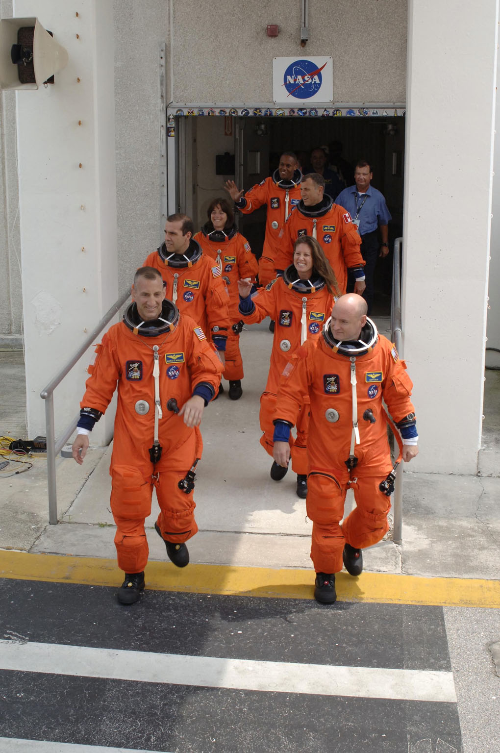 KENNEDY SPACE CENTER, FLA. -- The STS-118 crew stride out of the Operations and Checkout Building eager to get to Launch Pad 39A for launch of Space Shuttle Endeavour at 6:36 p.m. EDT. Leading the way are (left and right) Pilot Charlie Hobaugh and Commander Scott Kelly. Behind them, clockwise, are Mission Specialists Rick Mastracchio, teacher-turned-astronaut Barbara Morgan, Alvin Drew, Dave Williams and Tracy Caldwell. Williams represents the Canadian Space Agency. The STS-118 mission is the 22nd shuttle flight to the International Space Station. It will continue space station construction by delivering a third starboard truss segment, S5, and other payloads such as the SPACEHAB module and the external stowage platform 3. The 11-day mission may be extended to as many as 14 depending on the test of the Station-to-Shuttle Power Transfer System that will allow the docked shuttle to draw electrical power from the station and extend its visits to the orbiting lab. NASA/Kim Shiflett