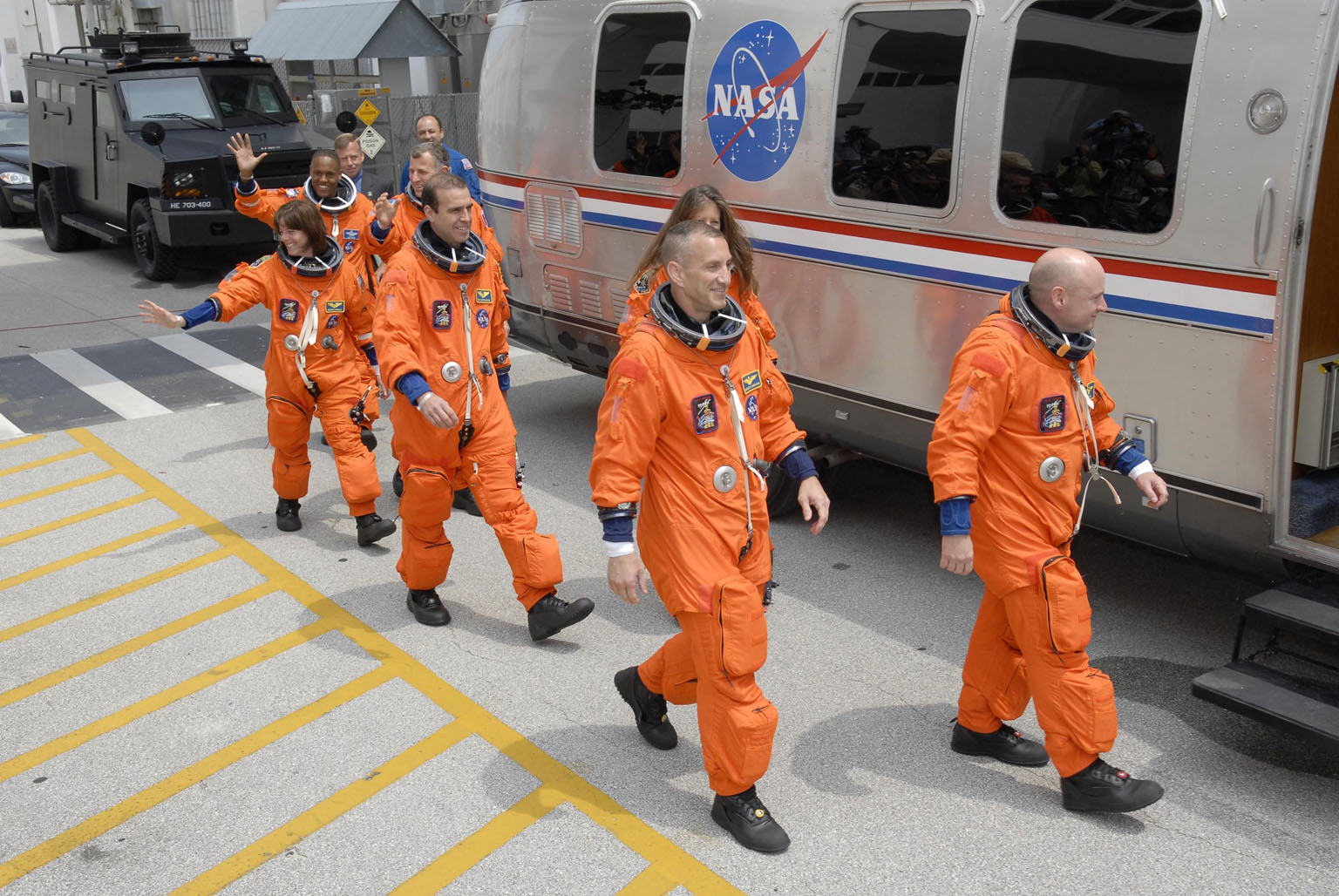 KENNEDY SPACE CENTER, FLA. -- The STS-118 crew waves to spectators as they head for the Astrovan. From left are Mission Specialists Alvin Drew, Barbara R. Morgan, Dave Williams and Rick Mastracchio, Pilot Charlie Hobaugh, Mission Specialist Tracy Caldwell and Commander Scott Kelly. The Astrovan will take them to Launch Pad 39A for final suit preparations before climbing into Space Shuttle Endeavour for launch at 6:36 p.m. EDT. The STS-118 mission is the 22nd shuttle flight to the International Space Station. It will continue space station construction by delivering a third starboard truss segment, S5, and other payloads such as the SPACEHAB module and the external stowage platform 3. The 11-day mission may be extended to as many as 14 depending on the test of the Station-to-Shuttle Power Transfer System that will allow the docked shuttle to draw electrical power from the station and extend its visits to the orbiting lab. NASA/Kim Shiflett