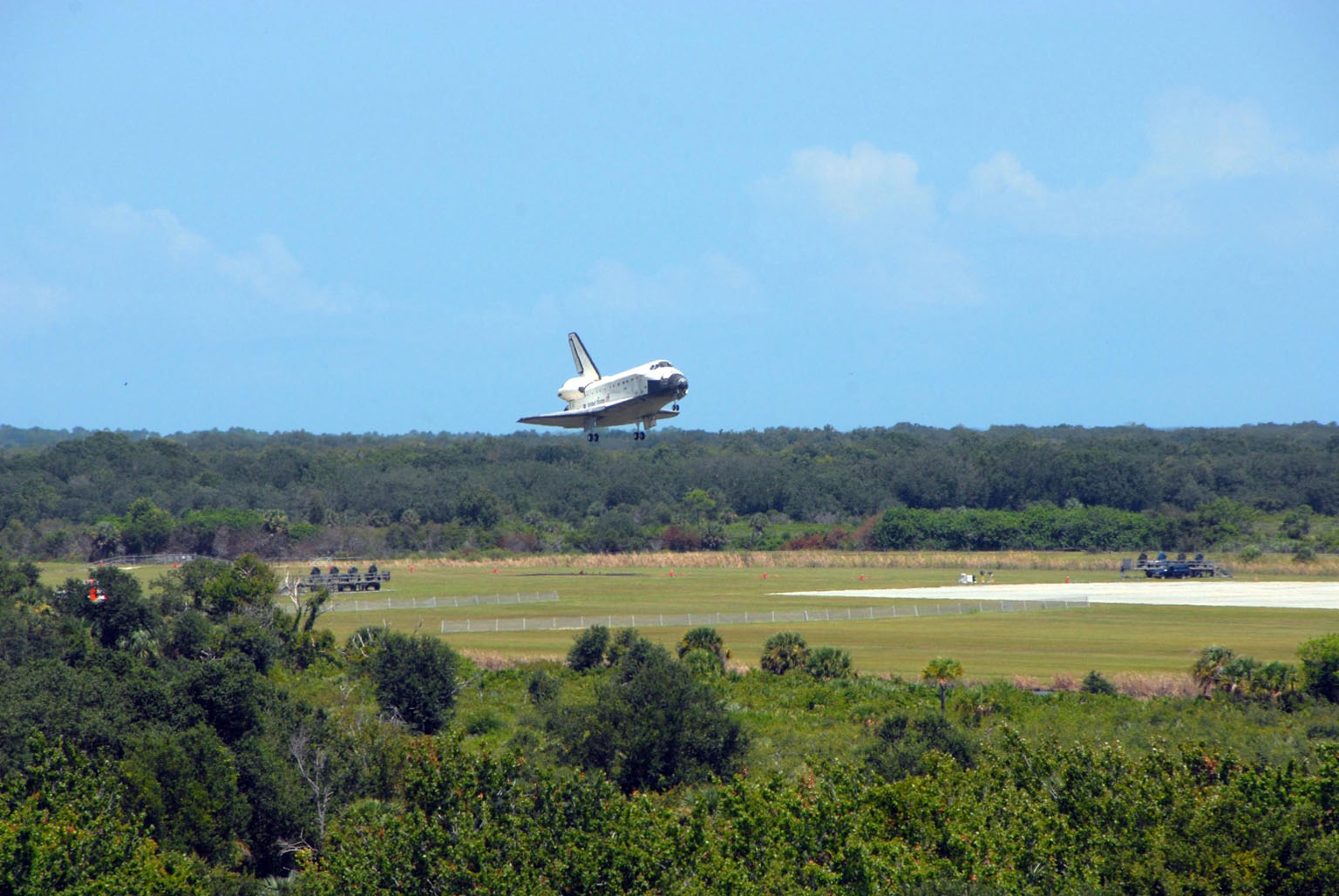 KENNEDY SPACE CENTER, FLA. -- Endeavour clears the trees as it approaches landing on runway 15 at NASA's Kennedy Space Center. The Space Shuttle Endeavour crew, led by Commander Scott Kelly, completes a 13-day mission to the International Space Station. The STS-118 mission began Aug. 8 and installed a new gyroscope, an external spare parts platform and another truss segment to the expanding station. Endeavour's main gear touched down at 12:32:16 p.m. EDT. Nose gear touchdown was at 12:32:29 p.m. and wheel stop was at 12:33:20 p.m. Endeavour traveled nearly 5.3 million miles, landing on orbit 201. STS-118 was the 119th space shuttle flight, the 22nd flight to the station, the 20th flight for Endeavour and the second of four missions planned for 2007. This was the 65th landing of an orbiter at Kennedy. Photo credit: NASA/Ken Thornsley
