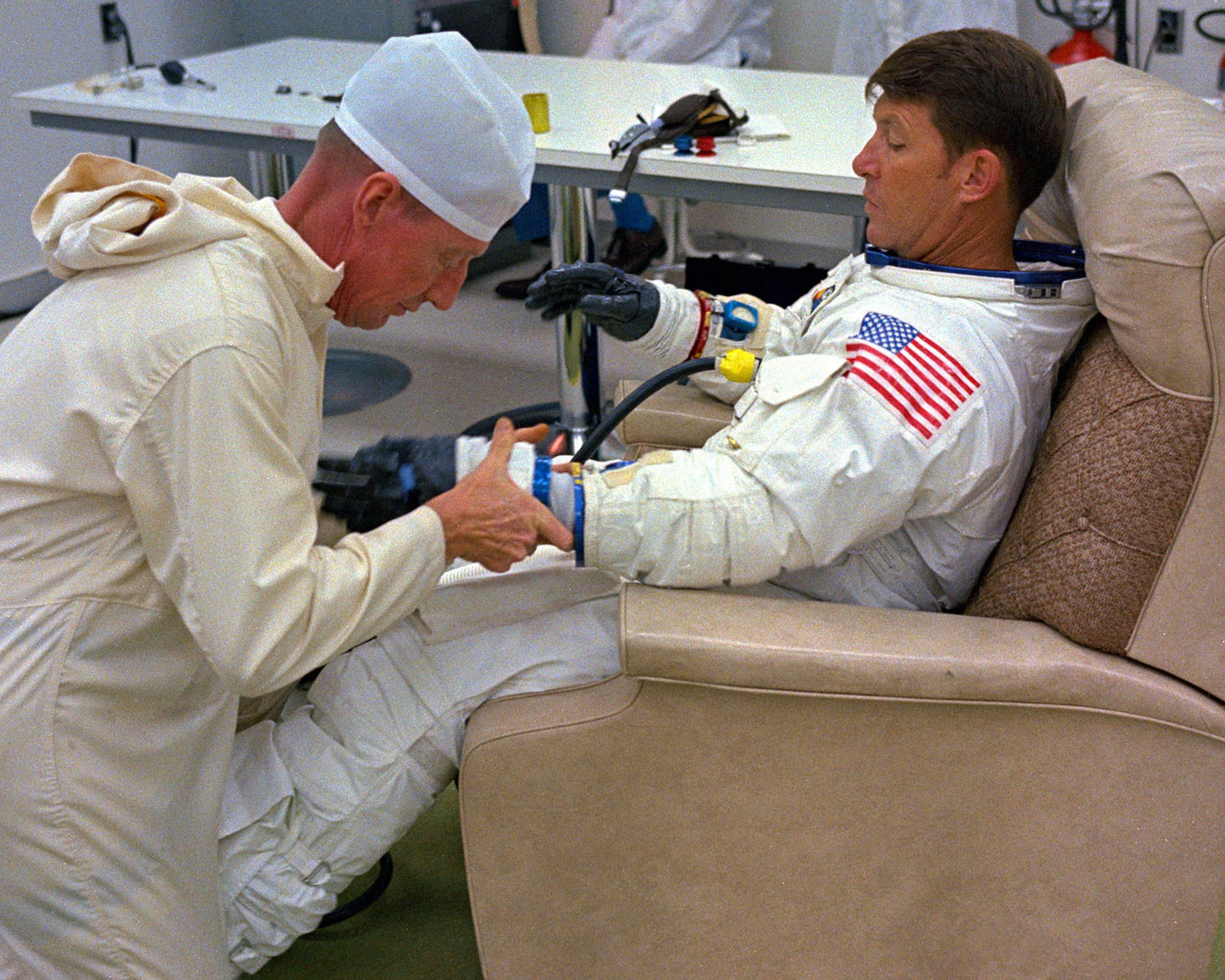 KENNEDY SPACE CENTER, FLA. - Spacesuit technician Clyde Teague adjusts the gloves on Apollo 7 Commander Walter M. Schirra Jr., during suiting operations. Astronaut Schirra, along with Command Module Pilot Donn F. Eisele, and Lunar Module Pilot Walter Cunningham, after being suited up, will depart for Launch Pad 34 and board their Saturn 1B rocket for the first manned lunar orbital mission. .