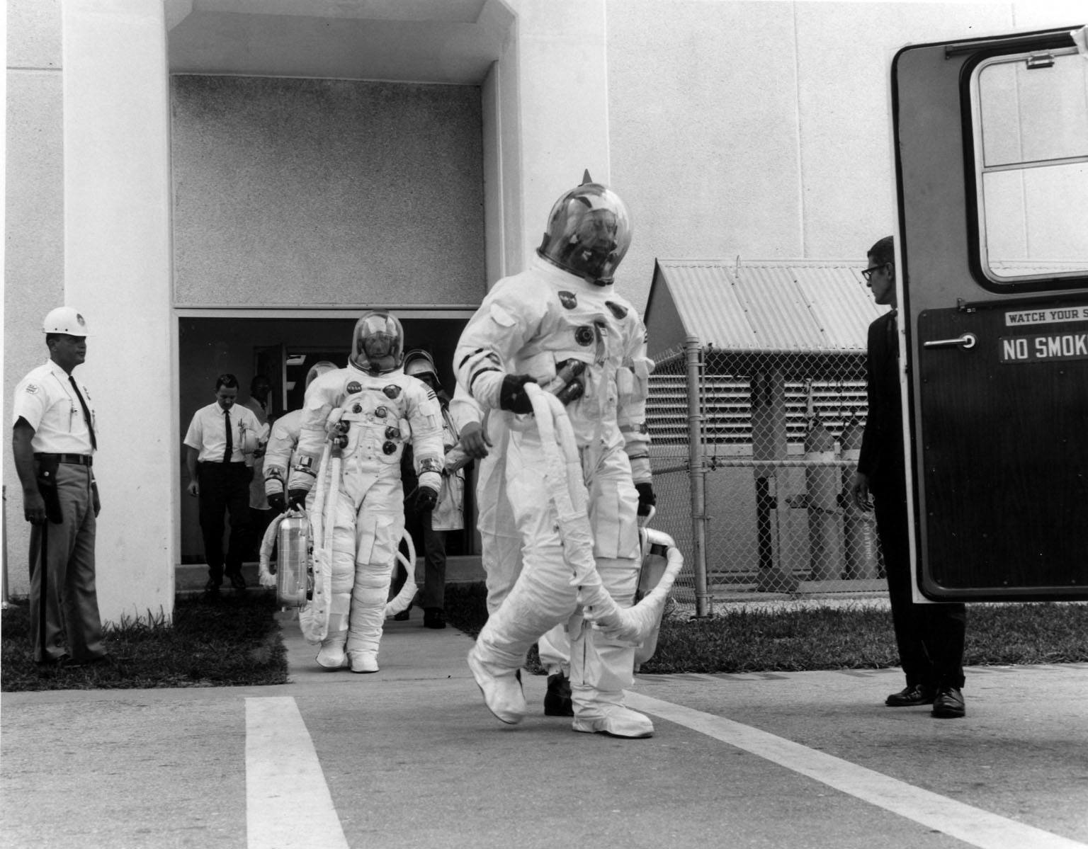 KENNEDY SPACE CENTER, FLA. -- Apollo 7 prime crew members, front to back, Donn F. Eisele, Walter M. Schirra Jr. and Walter Cunningham, leave the Kennedy Space Center's Manned Spacecraft Operations Building for a 20-minute ride in a transfer van to Cape Kennedy's Launch Complex 34, where they participated in a Space Vehicle Emergency Egress Test. The trio will pilot the National Aeronautics and Space Administration's first manned Apollo mission.