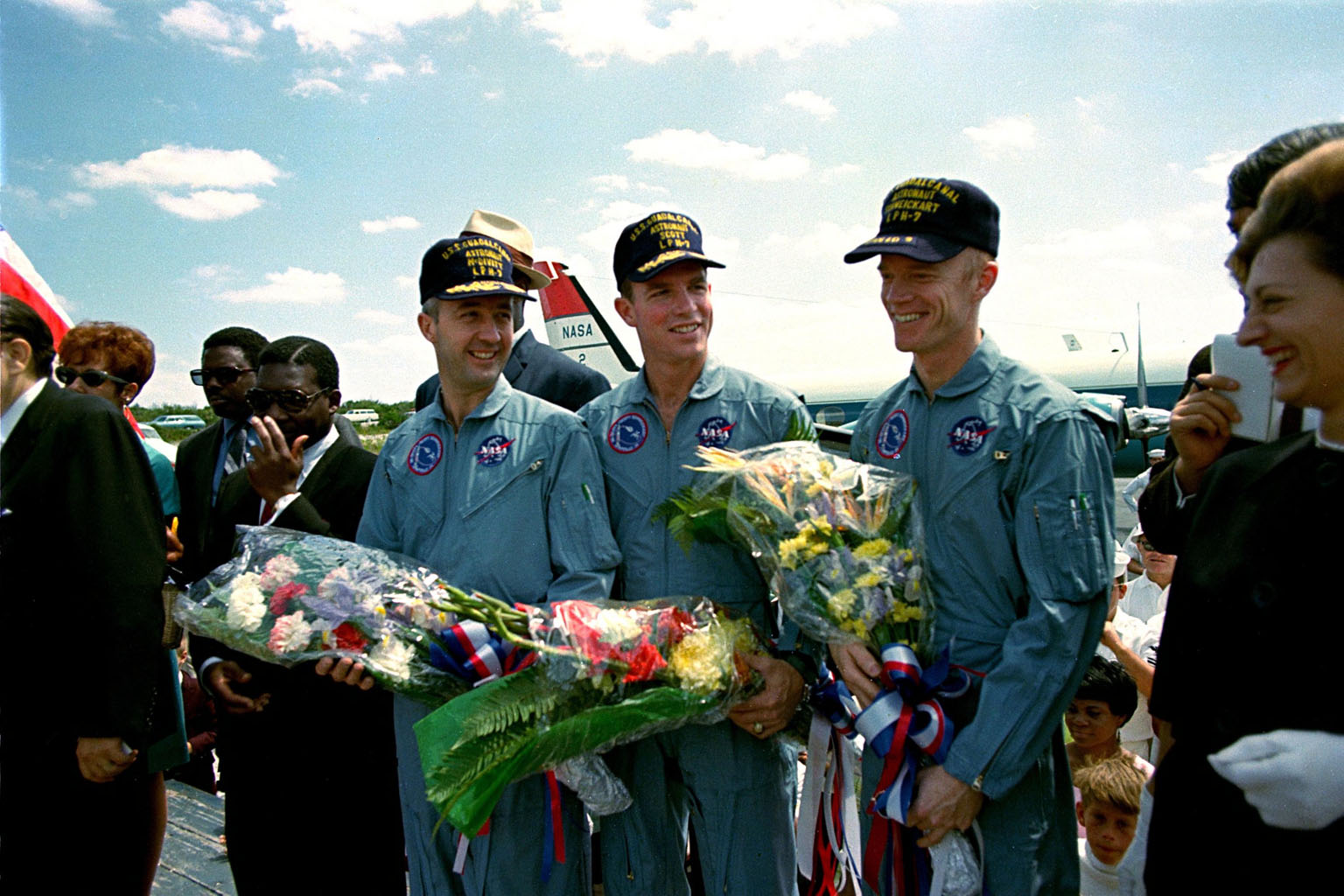 KENNEDY SPACE CENTER, FLA. - The Apollo 9 astronauts, left to right, James R. McDivitt, David R. Scott, and Russell L. Schweickart, receive flowers during a brief stopover on this Bahamian island while enroute back to Cape Kennedy. The three astronauts were launched from Cape Kennedy on March 3 from Launch Pad 39A and spent 10days in Earth orbit to test the Lunar Module Spacecraft in preparation for the upcoming manned lunar landings. Following their splashdown yesterday about 780 nautical miles southeast of Cape Kennedy, the three astronauts and their spacecraft were picked up by the USS Guadalcanal.