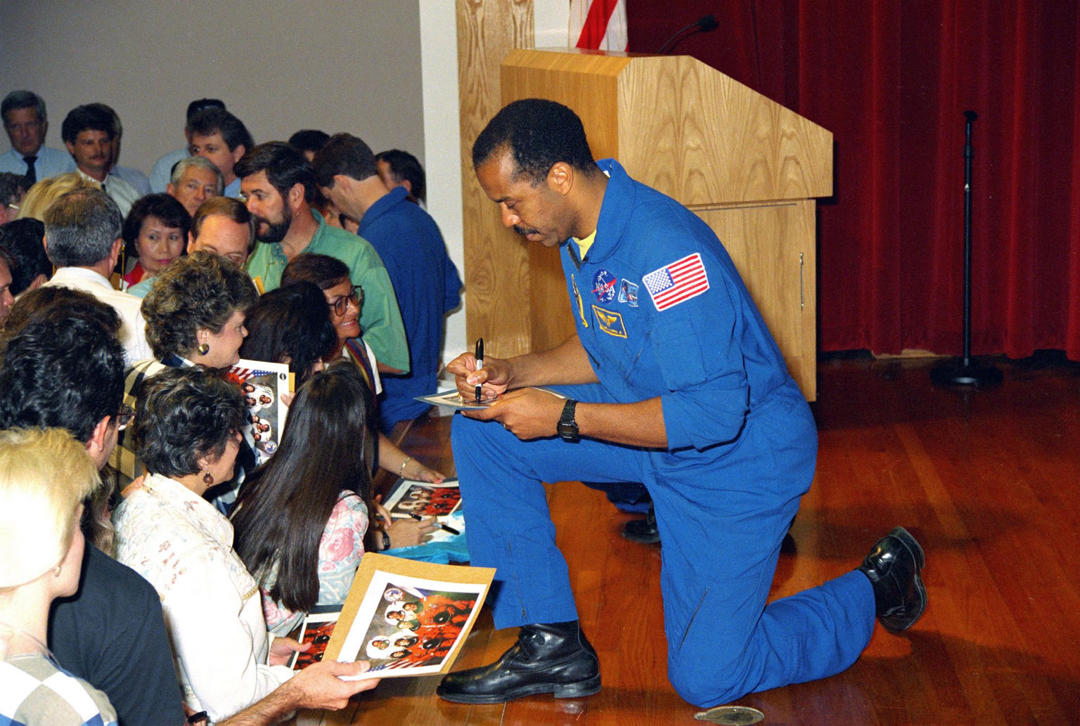 KENNEDY SPACE CENTER, FLA. -- STS-63 Mission Specialist Dr. Bernard Harris autographs copies of the crew photograph in the Training Auditorium during a March crew visit to thank employees for their help in ensuring a successful mission. The six-member crew on Discovery, who landed February 11 after an eight-day flight, included Mission Commander James Wetherbee, Pilot Eileen Collins (on the first flight of a female Shuttle pilot), and Mission Specialists Michael Foale, Janice Voss and Vladimir Titov. The mission featured another milestone, the first approach and flyaround of a Shuttle with Russian Space Station Mir. It was also the second flight of a russian cosmonaut on Shuttle and the third flight of the SPACEHAB module, which carried 20 experiments in biotechnology, advanced materials development, technology demonstrations and other measurements.