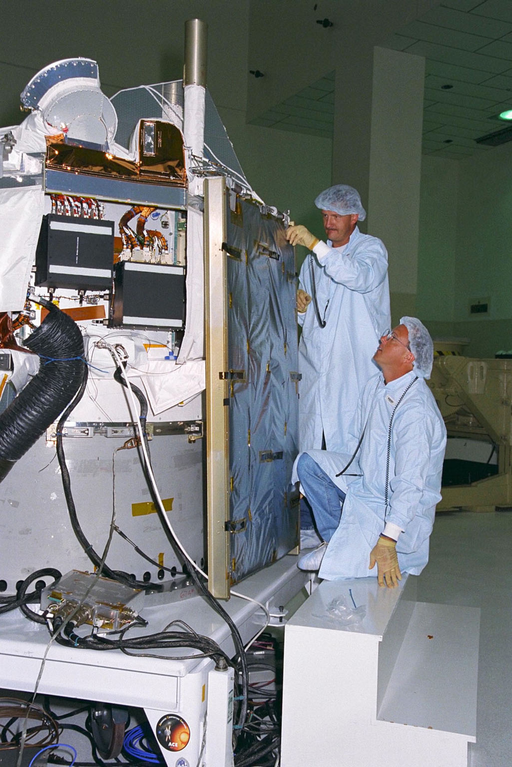 Applied Physics Laboratory Engineer Cliff Willey (kneeling) and Engineering Assistant Jim Hutcheson from Johns Hopkins University install solar array panels on the Advanced Composition Explorer (ACE) in KSC?s Spacecraft Assembly and Encapsulation Facility-II. Scheduled for launch on a Delta II rocket from Cape Canaveral Air Station on Aug. 25, ACE will study low-energy particles of solar origin and high-energy galactic particles for a better understanding of the formation and evolution of the solar system as well as the astrophysical processes involved. The ACE observatory will be placed into an orbit almost a million miles (1.5 million kilometers) away from the Earth, about 1/100 the distance from the Earth to the Sun. The collecting power of instrumentation aboard ACE is at least 100 times more sensitive than anything previously flown to collect similar data by NASA