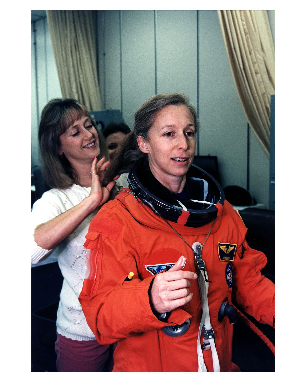 STS-81 Mission Specialist Marsha S. Ivins gets a helping hand from a suit technician as she prepares to don the helmet of her launch/entry suit in the suitup room of the Operations and Checkout (O&C) Building. She is the veteran of three Shuttle flights and became an astronaut in 1984. Among other responsibilities, Ivins will perform photo and video surveys of the Russian Mir space station and operate the Kidsat experiment camera on the orbiter?s aft flight deck. She and five crew members will shortly depart the O&C and head for Launch Pad 39B, where the Space Shuttle Atlantis will lift off during a 7-minute window that opens at 4:27 a.m. EST, January 12