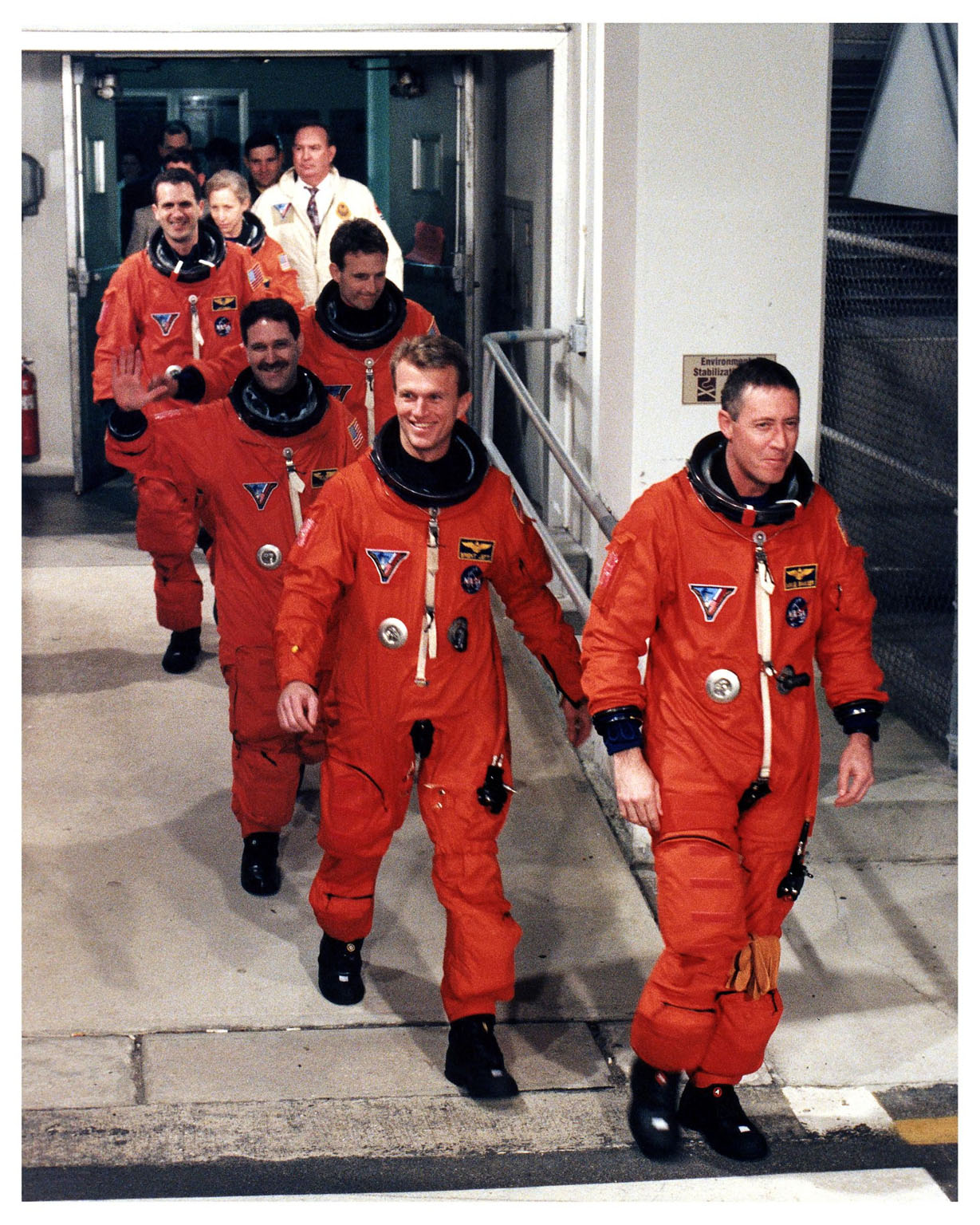 """Greeted by cheers from wellwishers at KSC and eager for their venture into space on the fifth Shuttle-Mir docking mission, the STS-81 astronauts depart the Operations and Checkout Building on their way to Launch Pad 39B. Leading the six-member crew is Mission Commander Michael A. Baker, followed by Pilot Brent W. Jett, Jr. Behind them are Mission Specialists John M. Grunsfeld, Jerry Linenger, Peter J. K. """"Jeff"""" Wisoff, and Marsha S. Ivins. Their trip to the pad will take about 25 minutes aboard the Astrovan. Once there, they will take their positions in the crew cabin of the Space Shuttle Atlantis to await a liftoff during a seven-minute window that will open at 4:27 a.m. EST, January 12"""