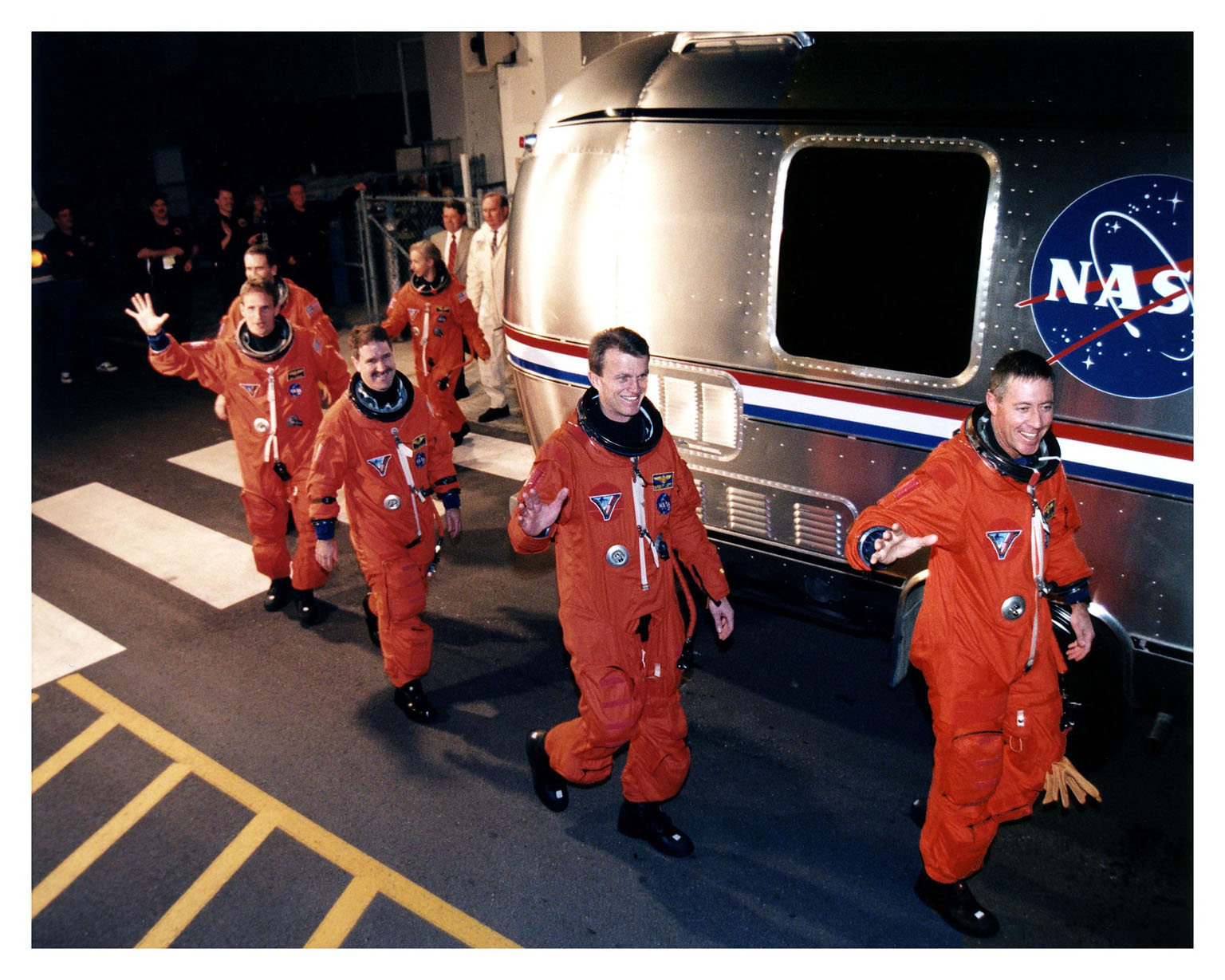 """Greeted by cheers from wellwishers at KSC and eager for their venture into space on the fifth Shuttle-Mir docking mission, the STS-81 astronauts depart the Operations and Checkout Building and board the Astrovan for their 25-minute trip to Launch Pad 39B. Leading the six-member crew is Mission Commander Michael A. Baker, followed by Pilot Brent W. Jett, Jr. Behind them are Mission Specialists John M. Grunsfeld, Jerry Linenger, Peter J. K. """"Jeff"""" Wisoff, and Marsha S. Ivins. Once at the pad, they will take their positions in the crew cabin of the Space Shuttle Atlantis to await a liftoff during a seven-minute window that will open at 4:27 a.m. EST, January 12"""