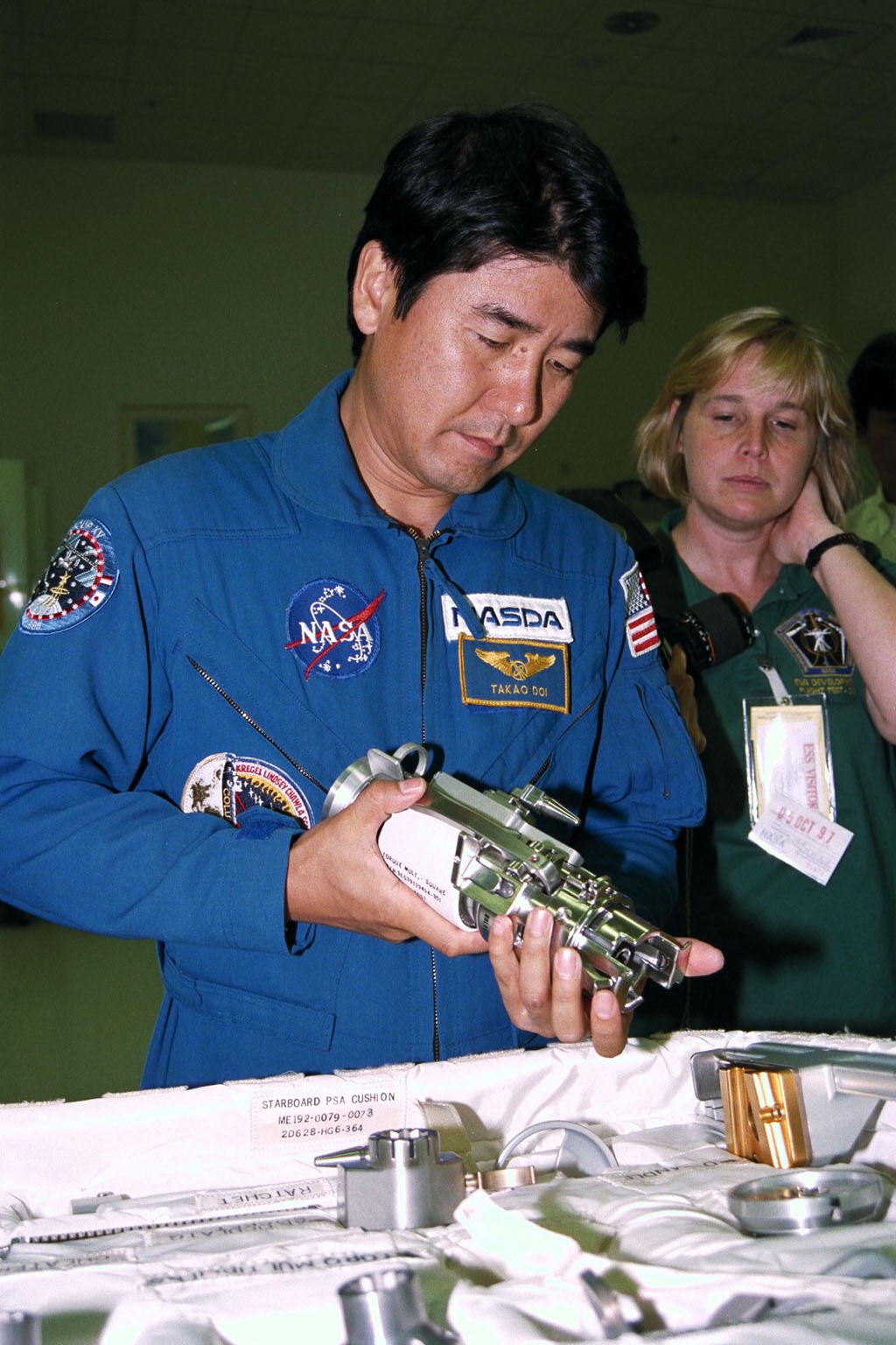 STS-87 Mission Specialist Takao Doi , Ph.D., of the National Space Development Agency of Japan, participates in the Crew Equipment Integration Test (CEIT) in Kennedy Space Center?s (KSC's) Vertical Processing Facility. Glenda Laws, the extravehicular activity (EVA) coordinator, Johnson Space Center, stands behind Dr. Doi. The CEIT gives astronauts an opportunity to get a hands-on look at the payloads with which they will be working on-orbit. STS-87 will be the fourth United States Microgravity Payload and flight of the Spartan-201 deployable satellite. During the mission, Dr. Doi will be the first Japanese astronaut to perform a spacewalk. STS-87 is scheduled for a Nov. 19 liftoff from KSC