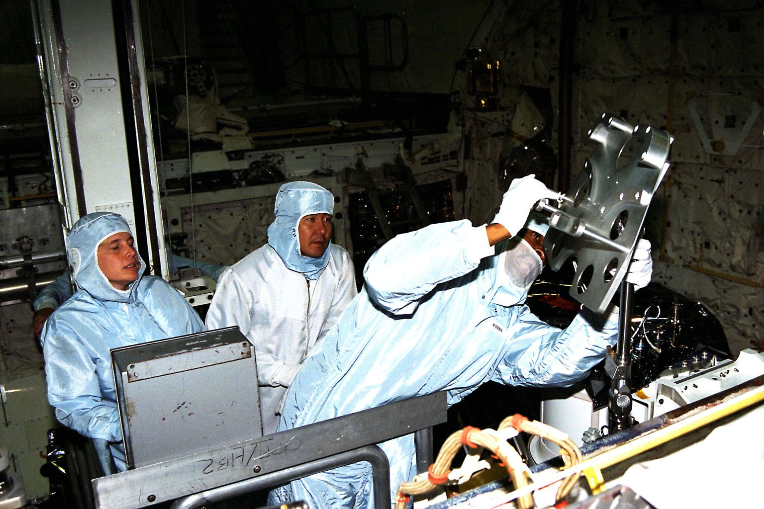 Participating in the Crew Equipment Integration Test (CEIT) at Kennedy Space Center are STS-87 crew members, assisted by Glenda Laws, extravehicular activity (EVA) coordinator, Johnson Space Center, at left. Next to Laws is Mission Specialist Takao Doi, Ph.D., of the National Space Development Agency of Japan, who is looking on as Mission Specialist Winston Scott gets a hands-on look at some of the equipment. The STS-87 mission will be the fourth United States Microgravity Payload and flight of the Spartan-201 deployable satellite. During the mission, scheduled for a Nov. 19 liftoff from KSC, Dr. Doi and Scott will both perform spacewalks