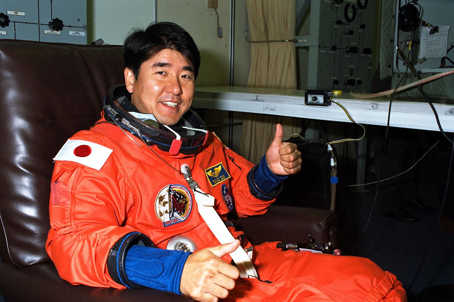 STS-87 Mission Specialist Takao Doi, Ph.D., of the National Space Development Agency of Japan, gives a ?thumbs up? in his launch and entry suit in the Operations and Checkout Building. He and the five other crew members will depart shortly for Launch Pad 39B, where the Space Shuttle Columbia awaits liftoff on a 16-day mission to perform microgravity and solar research. Dr. Doi is scheduled to perform an extravehicular activity spacewalk with Mission Specialist Winston Scott during STS-87