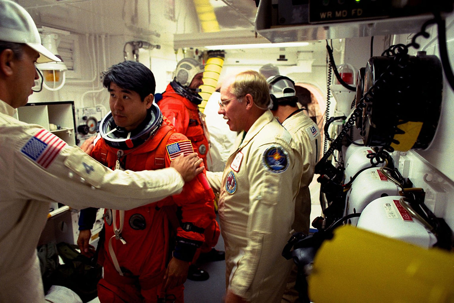 STS-87 Mission Specialist Takao Doi, Ph.D., of the National Space Development Agency of Japan, is assisted with his ascent and re-entry flight suit by Dave Law, USA mechanical technician, in the white room at Launch Pad 39B as Dr. Doi prepares to enter the Space Shuttle orbiter Columbia on launch day. At right wearing glasses is Danny Wyatt, NASA quality assurance specialist. STS-87 is the fourth flight of the United States Microgravity Payload and Spartan-201. The 16-day mission will include a spacewalk by Dr. Doi and Mission Specialist Winston Scott