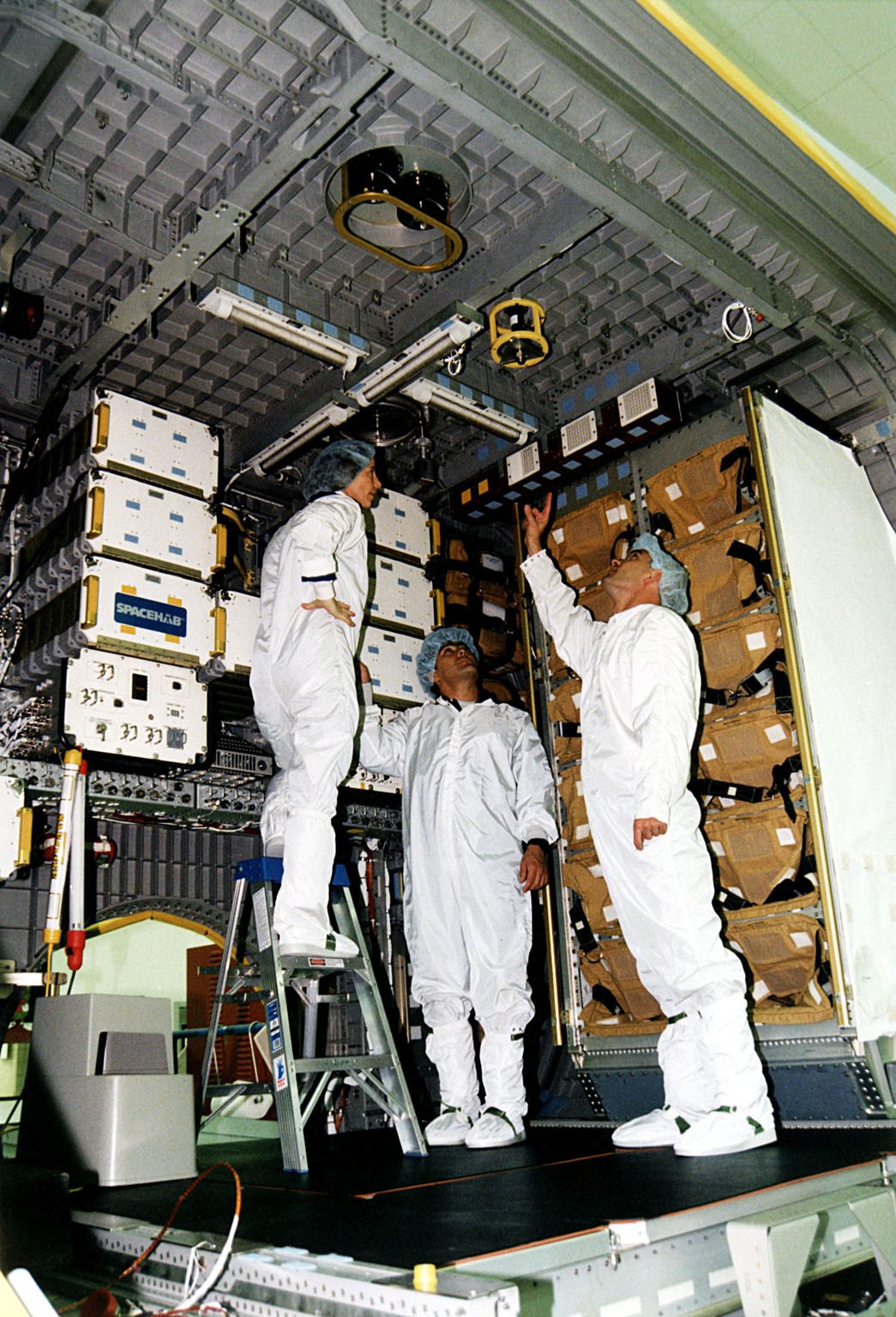 KENNEDY SPACE CENTER, FLA. -- Several STS-89 crew members participate in the Crew Equipment Interface Test (CEIT) inside the SPACEHAB module at the SPACEHAB Payload Processing Facility at Port Canaveral in preparation for the mission, slated to be the first Shuttle launch of 1998. From left to right are Mission Specialists Bonnie Dunbar, Ph.D., and Salizhan Sharipov of the Russian Space Agency, and Pilot Joe Edwards. The CEIT gives astronauts an opportunity to get a hands-on look at the payloads with which they will be working on-orbit. STS-89 will be the eighth of nine scheduled Mir dockings and will include a double module of SPACEHAB, used mainly as a large pressurized cargo container for science, logistical equipment and supplies to be exchanged between the orbiter Endeavour and the Russian Space Station Mir. The nine-day flight of STS-89 also is scheduled to include the transfer of the seventh American to live and work aboard the Russian orbiting outpost. Liftoff of Endeavour and its seven-member crew is targeted for Jan. 15, 1998, at 1:03 a.m. EST from Launch Pad 39A