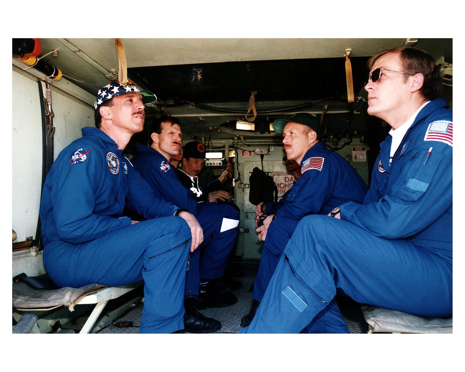 """STS-82 crew members ride in and learn how to operate an M-113 armored personnel carrier during Terminal Countdown Demonstration Test (TCDT) activities prior to launch. The four crew members dressed in their blue flight suits and visible here are, from left, Pilot Scott J. """"Doc"""" Horowitz, Mission Specialist Joseph R. """"Joe"""" Tanner, Mission Commander Kenneth D. Bowersox and Payload Commander Mark C. Lee. George Hoggard, a training officer with KSC Fire Services, is visible in the background at left. The 10-day STS-82 flight, which will be the second Hubble Space Telescope servicing mission, is targeted for a Feb. 11 liftoff"""