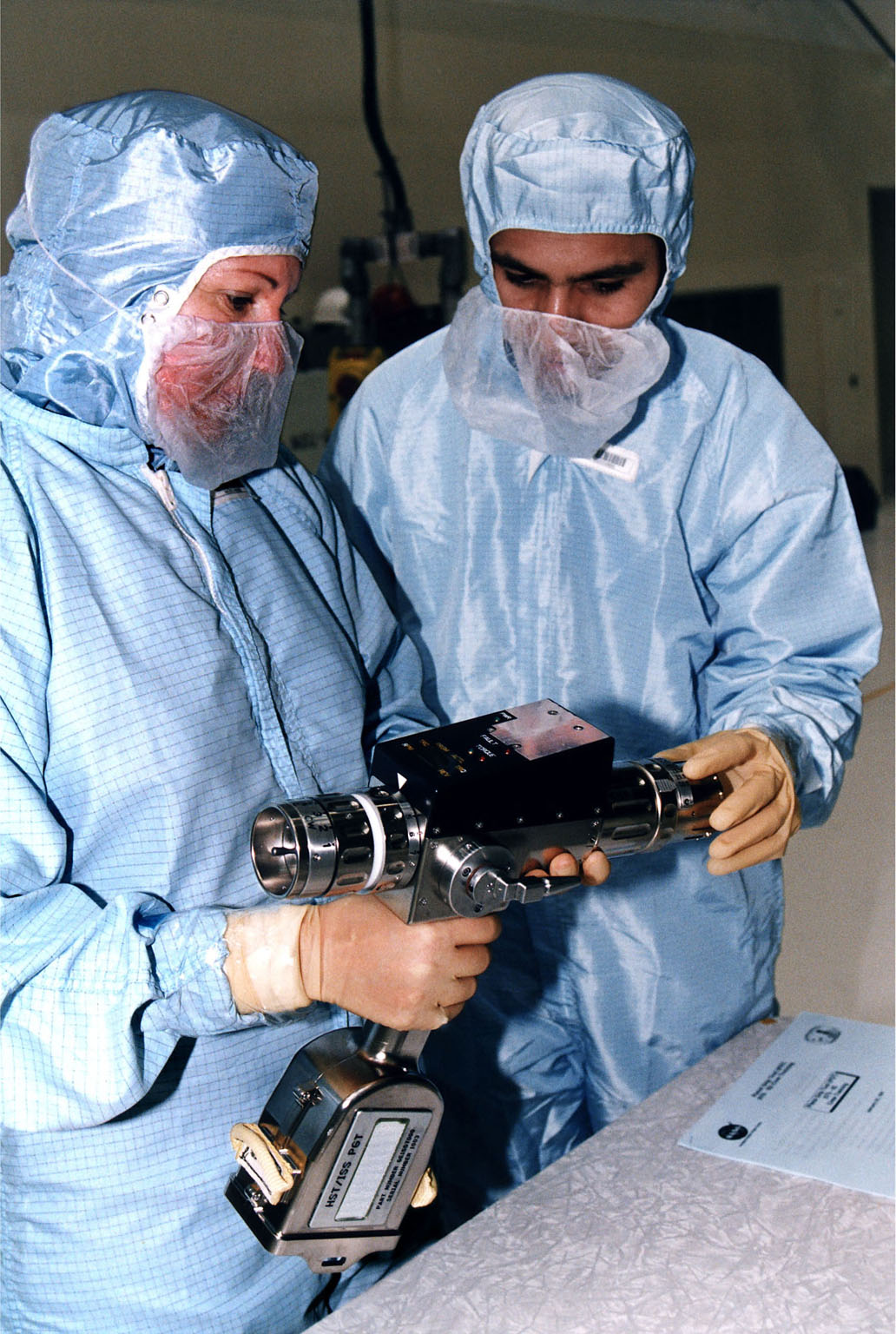 KENNEDY SPACE CENTER, FLA. - In KSC's Vertical Processing Facility, Louise Kleba of the Vehicle Integration Test Team (VITT) and engineer Devin Tailor of Goddard Space Flight Center examine the Pistol Grip Tool (PGT), which was designed for use by astronauts during spacewalks. The PGT is a self-contained, micro-processor controlled, battery-powered tool. It also can be used as a nonpowered ratchet wrench. The experiences of the astronauts on the first Hubble Space Telescope (HST) servicing mission led to recommendations for this smaller, more efficient tool for precision work during spacewalks. The PGT will be used on the second HST servicing mission, STS-82. Liftoff aboard Discovery is scheduled Feb. 11.