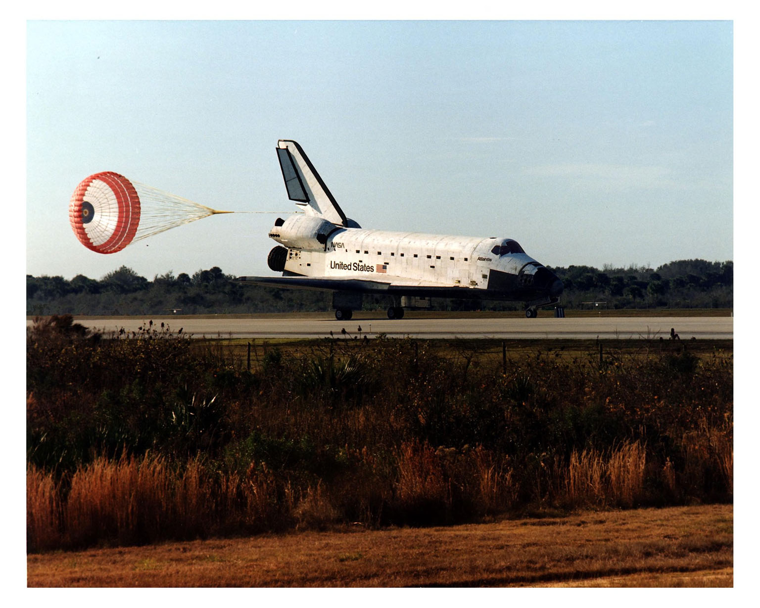 """KENNEDY SPACE CENTER, FLA. -- With its drag chute deployed, the Space Shuttle orbiter Atlantis touches down on Runway 33 on the second opportunity at 9:22:44 a.m. EST Jan. 22 to conclude the fifth Shuttle-Mir docking mission and return NASA astronaut John Blaha to Earth after four months in space. At main gear touchdown, the STS-81 mission duration was 10 days, 4 hours, 55 minutes. This was the 34th KSC landing in Shuttle history. Mission Commander Michael A. Baker flew Atlantis to a perfect landing, with help from Pilot Brent W. Jett, Jr. Other returning STS-81 crew members are Mission Specialists John M.Grunsfeld, Peter J. K. """"Jeff"""" Wisoff and Marsha S. Ivins. Atlantis also brought back experiment samples from the Russian space station Mir for analysis on Earth, along with Russian logistics equipment"""