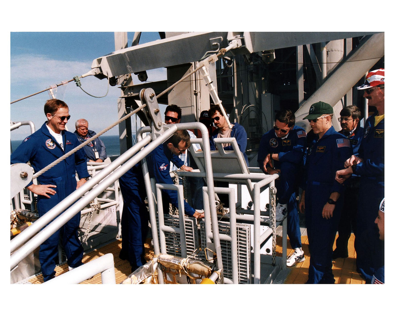 """KENNEDY SPACE CENTER, Fla. --STS-82 crew members and other onlookers at Launch Pad 39A watch as STS-82 Mission Specialist Steven L. Smith becomes familiar with operation of the slidewire baskets. The slidewire baskets are part of the emergency egress system at the pad. The crew are at KSC to participate in the Terminal Countdown Demonstration Test (TCDT), a dress rehearsal for launch. In their blue flight suits, from left, are Payload Commander Mark C. Lee, Smith, Mission Specialist Gregory J. Harbaugh, Mission Commander Kenneth D. Bowersox and Mission Specialist Joseph R. """"Joe"""" Tanner. The seven-member STS-82 crew will conduct the second Hubble Space Telescope servicing mission. Liftoff of the 10-day flight is scheduled Feb. 11"""
