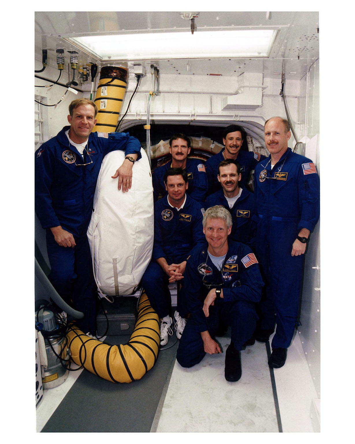 """KENNEDY SPACE CENTER, Fla. -- At Launch Pad 39A, STS-82 crew members pose for a group photo outside the entrance to the Space Shuttle Discovery?s crew cabin. Kneeling in front is Mission Specialist Steven A. Hawley. Payload Commander Mark C. Lee is at far left. In second row behind Hawley, from left, are Mission Specialists Gregory J. Harbaugh and Steven L. Smith, and Mission Commander Kenneth D. Bowersox. In back, from left, are Mission Specialists Joseph R. """"Joe"""" Tanner and Pilot Scott J. """"Doc"""" Horowitz. The crew are at KSC to participate in the Terminal Countdown Demonstration Test (TCDT), a dress rehearsal for launch. The seven-member crew will conduct the second Hubble Space Telescope servicing mission. Liftoff of the 10-day flight is scheduled Feb. 11"""