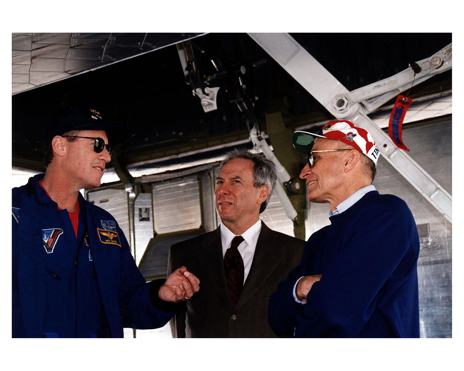 KENNEDY SPACE CENTER, FLA. -- NASA Administrator Daniel S. Goldin (center) and KSC Director of Shuttle Operations Robert B. Sieck (right) discuss the successful conclusion of the STS-81 mission with Mission Commander Michael A. Baker (left). They are underneath the Space Shuttle orbiter Atlantis after the space plane landed on Runway 33 at the KSC Shuttle Landing Facility at 9:22:44 a.m. EST Jan. 22 to conclude the fifth Shuttle-Mir docking mission. At main gear touchdown, the STS-81 mission duration was 10 days, 4 hours, 55 minutes. This was the 34th KSC landing in Shuttle history