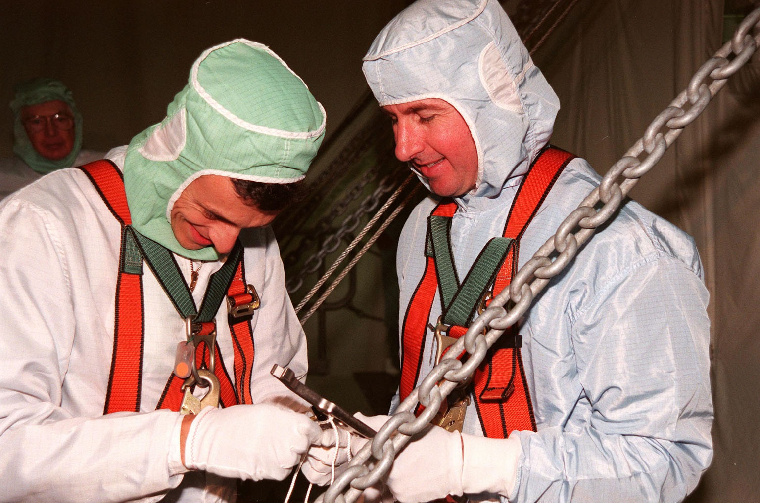 During the Crew Equipment Interface Test (CEIT) in the payload bay of Discovery, STS-95 Mission Specialist Pedro Duque (left), of the European Space Agency, tethers a wrench held by Mission Specialist Stephen K. Robinson (right) that they will use during the mission. The CEIT gives astronauts an opportunity for a hands-on look at the payloads and equipment with which they will be working on orbit. The launch of the STS-95 mission is scheduled for Oct. 29, 1998. The mission includes research payloads such as the Spartan solar-observing deployable spacecraft, the Hubble Space Telescope Orbital Systems Test Platform, the International Extreme Ultraviolet Hitchhiker, as well as the SPACEHAB single module with experiments on space flight and the aging process