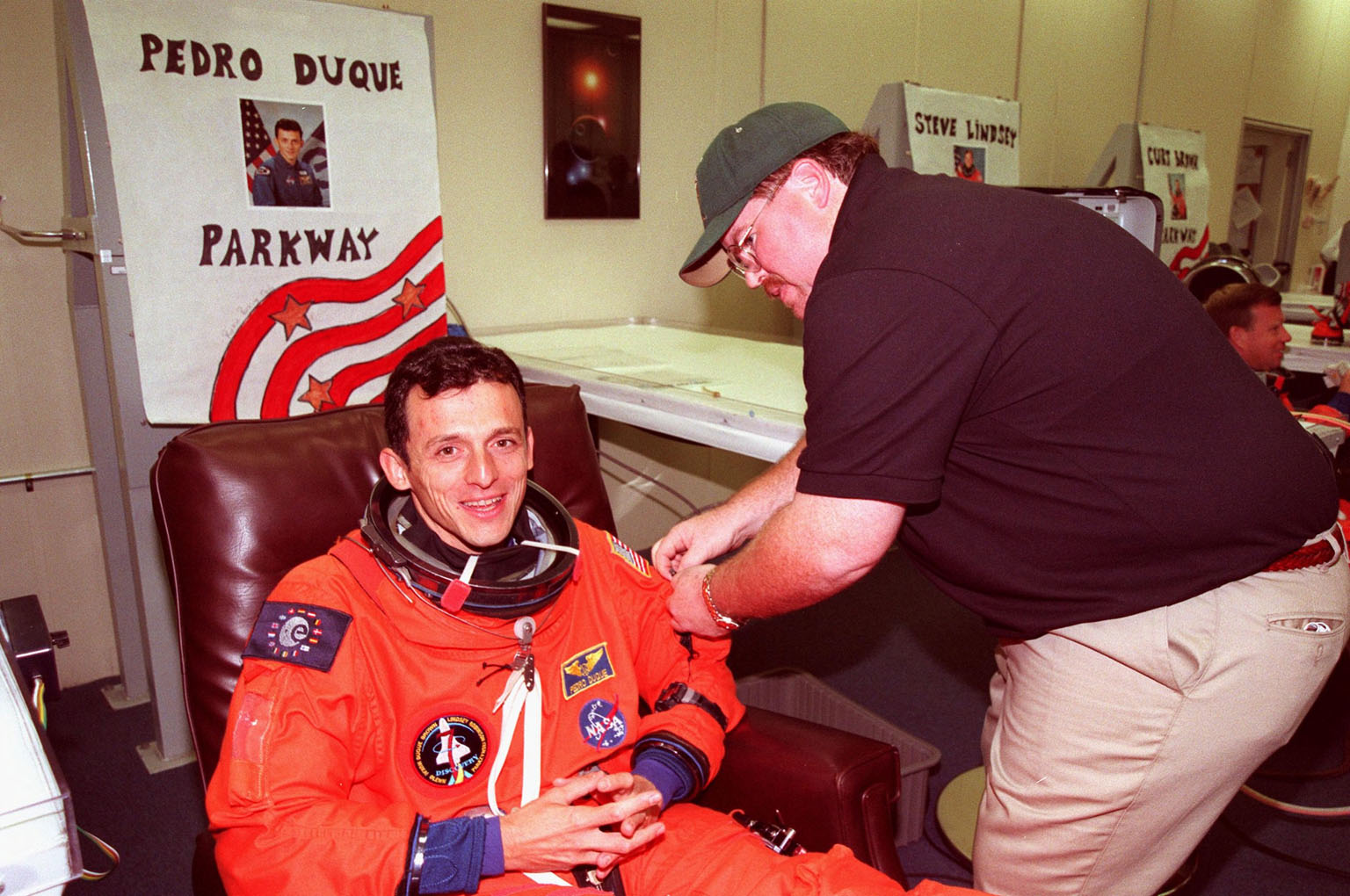 STS-95 Mission Specialist Pedro Duque of Spain, with the European Space Agency, is helped with his flight suit by suit tech Tommy McDonald in the Operations and Checkout Building. The final fitting takes place prior to the crew walkout and transport to Launch Pad 39B. Targeted for launch at 2 p.m. EST on Oct. 29, the mission is expected to last 8 days, 21 hours and 49 minutes, and return to KSC at 11:49 a.m. EST on Nov. 7. The STS-95 mission includes research payloads such as the Spartan solar-observing deployable spacecraft, the Hubble Space Telescope Orbital Systems Test Platform, the International Extreme Ultraviolet Hitchhiker, as well as the SPACEHAB single module with experiments on space flight and the aging process