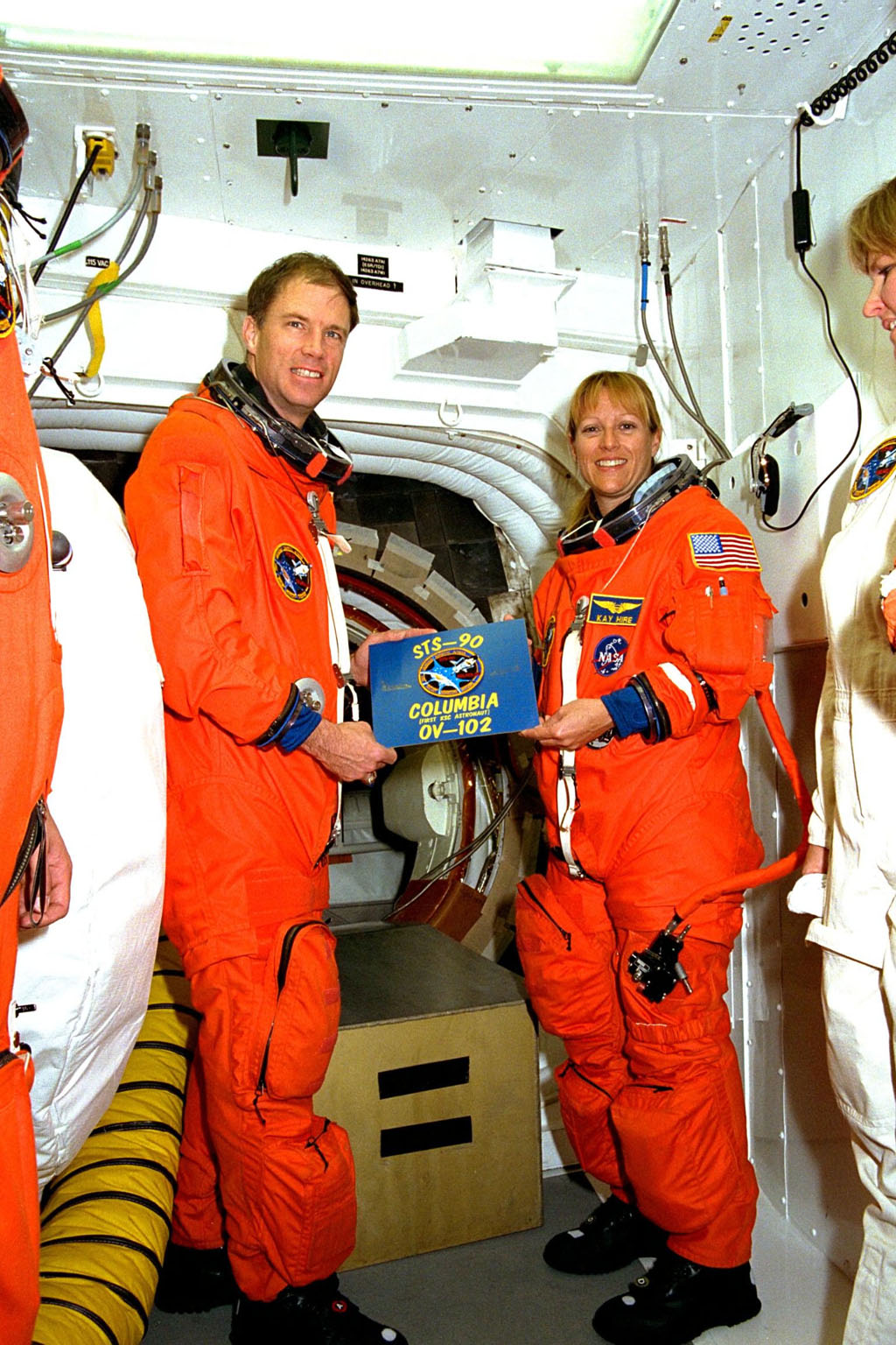 The crew of STS-90 participate in Terminal Countdown Demonstration Test (TCDT) activities at KSC's Launch Pad 39B. The TCDT is held at KSC prior to each Space Shuttle flight to provide crews with the opportunity to participate in simulated countdown activities. Here, STS-90 Commander Richard Searfoss and Mission Specialist Kathryn (Kay) Hire hold the mission patch with orbiter information. Columbia is targeted for launch of STS-90 on April 16 at 2:19 p.m. EDT and will be the second mission of 1998. The mission is scheduled to last nearly 17 days