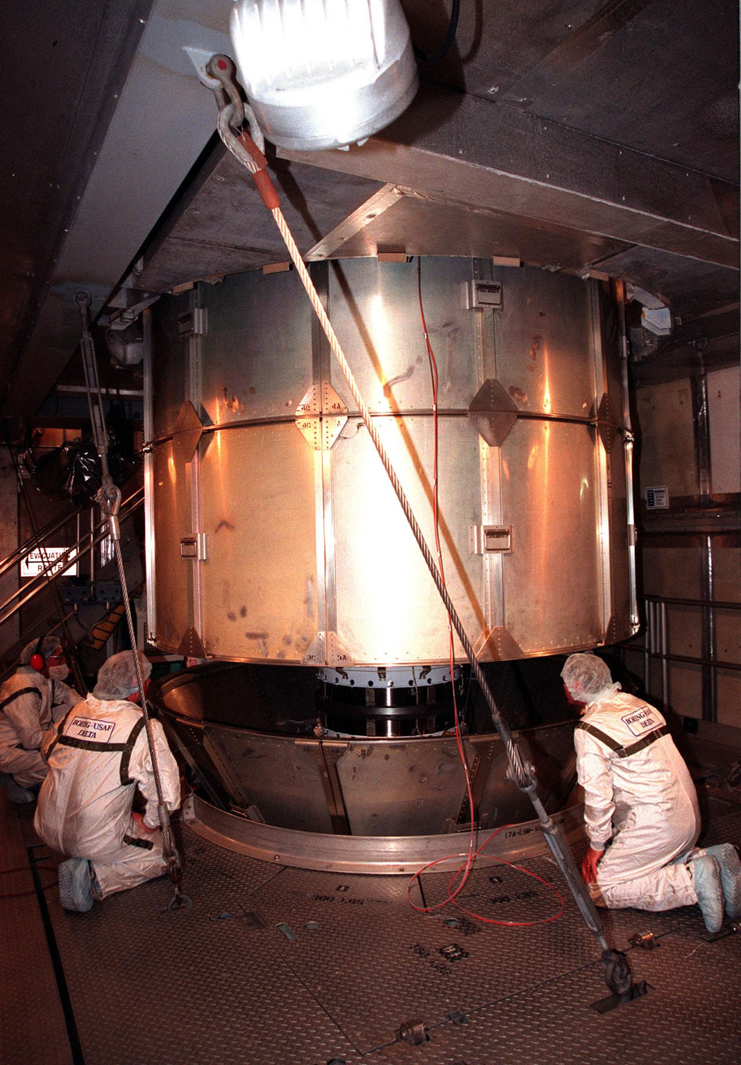 At Launch Pad 17-A, Cape Canaveral Air Station, workers watch as the protective canister is lifted from the Stardust spacecraft. Preparations continue for liftoff of the Boeing Delta II rocket carrying Stardust on Feb. 6. Stardust is destined for a close encounter with the comet Wild 2 in January 2004. Using a silicon-based substance called aerogel, Stardust will capture comet particles flying off the nucleus of the comet. The spacecraft also will bring back samples of interstellar dust. These materials consist of ancient pre-solar interstellar grains and other remnants left over from the formation of the solar system. Scientists expect their analysis to provide important insights into the evolution of the sun and planets and possibly into the origin of life itself. The collected samples will return to Earth in a sample return capsule to be jettisoned as Stardust swings by Earth in January 2006