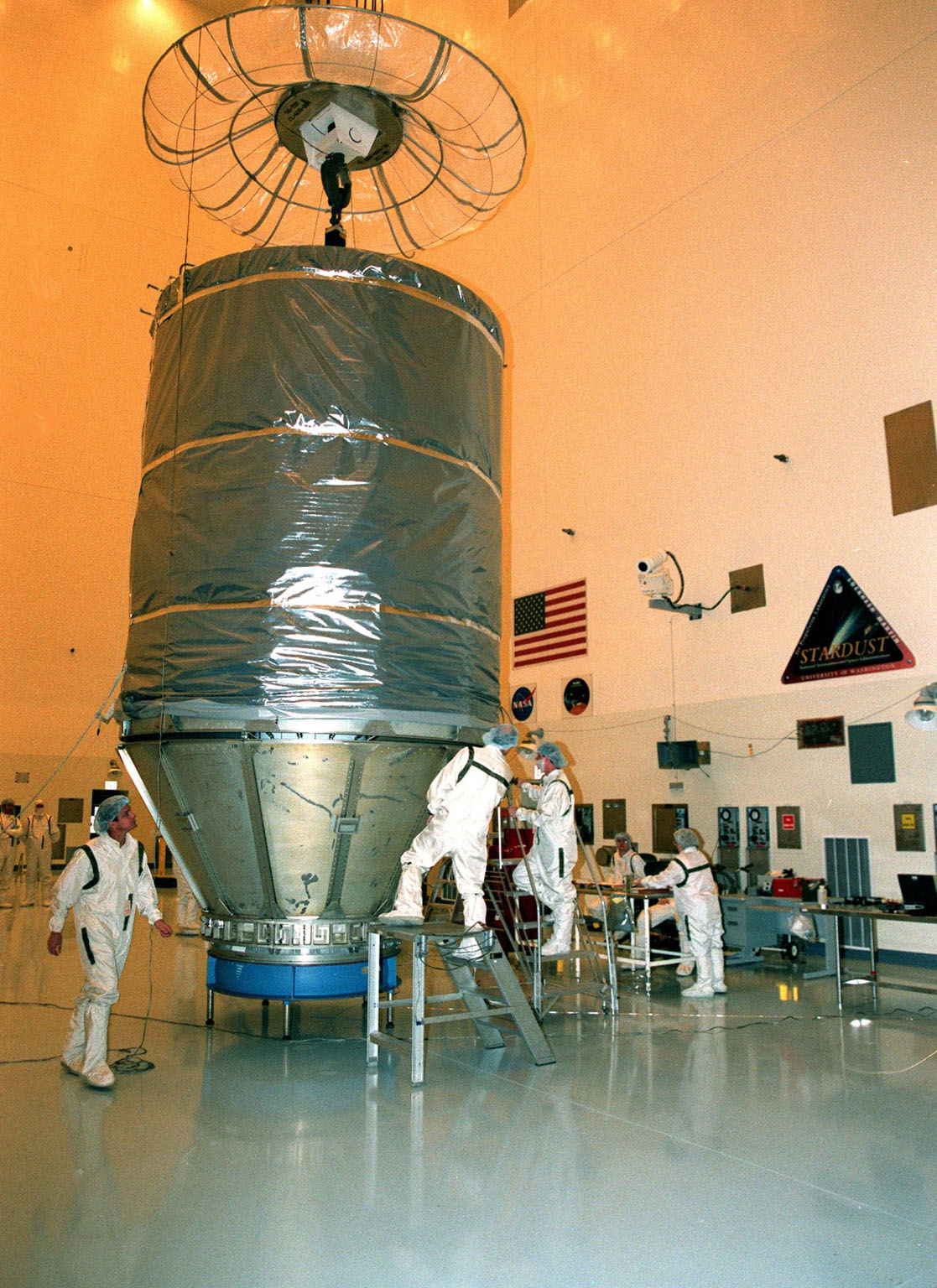 In the Payload Hazardous Servicing Facility, workers check the final adjustments on the protective canister enclosing the Stardust spacecraft. Stardust will be moved to Launch Pad 17-A, Cape Canaveral Air Station, for launch preparations. The spacecraft is targeted for liftoff on Feb. 6 aboard a Boeing Delta II rocket for a close encounter with the comet Wild 2 in January 2004. Using a silicon-based substance called aerogel, Stardust will capture comet particles flying off the nucleus of the comet. The spacecraft also will bring back samples of interstellar dust. These materials consist of ancient pre-solar interstellar grains and other remnants left over from the formation of the solar system. Scientists expect their analysis to provide important insights into the evolution of the sun and planets and possibly into the origin of life itself. The collected samples will return to Earth in a sample return capsule to be jettisoned as Stardust swings by Earth in January 2006